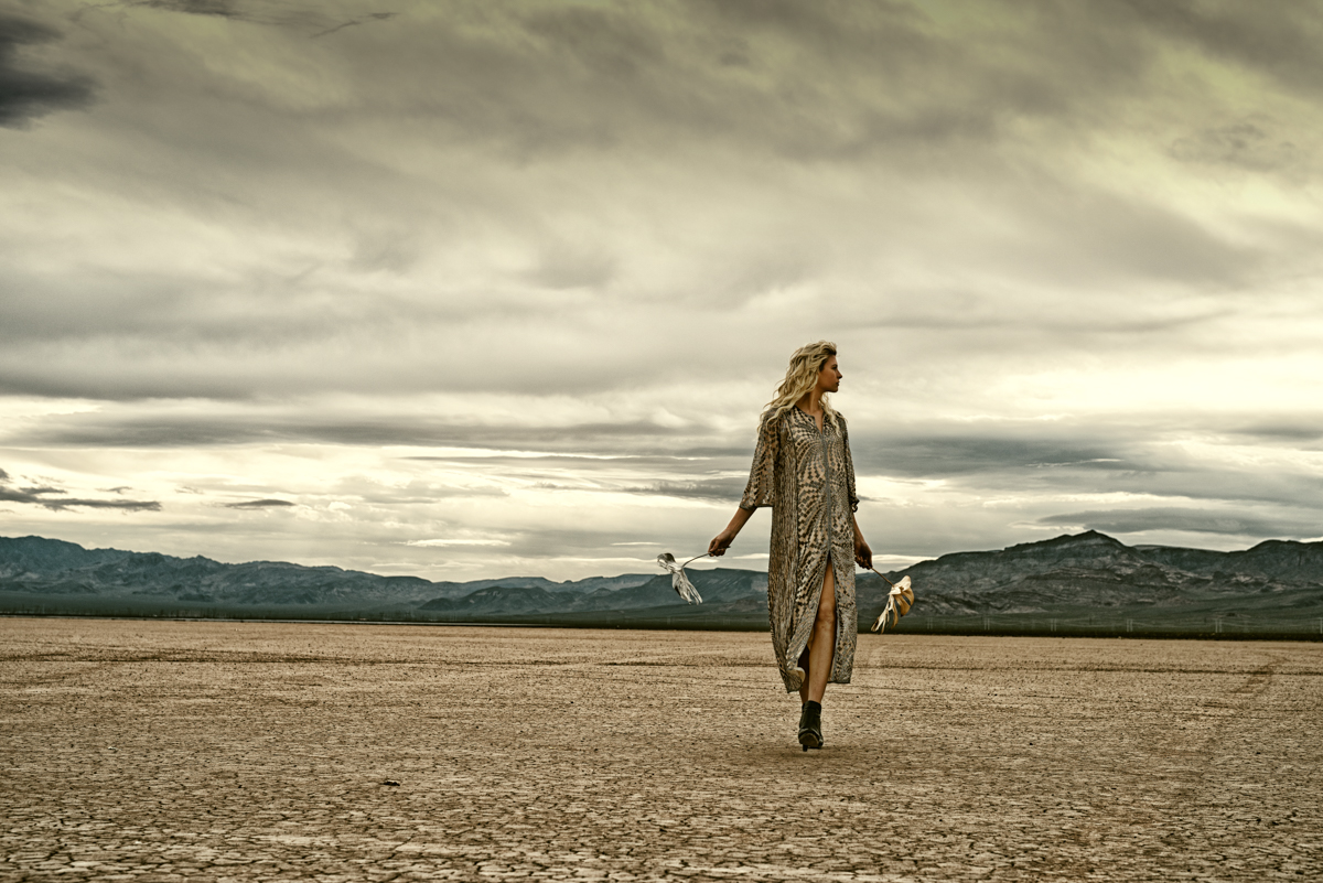 model on dry lake bed with gold dress and gold leaves