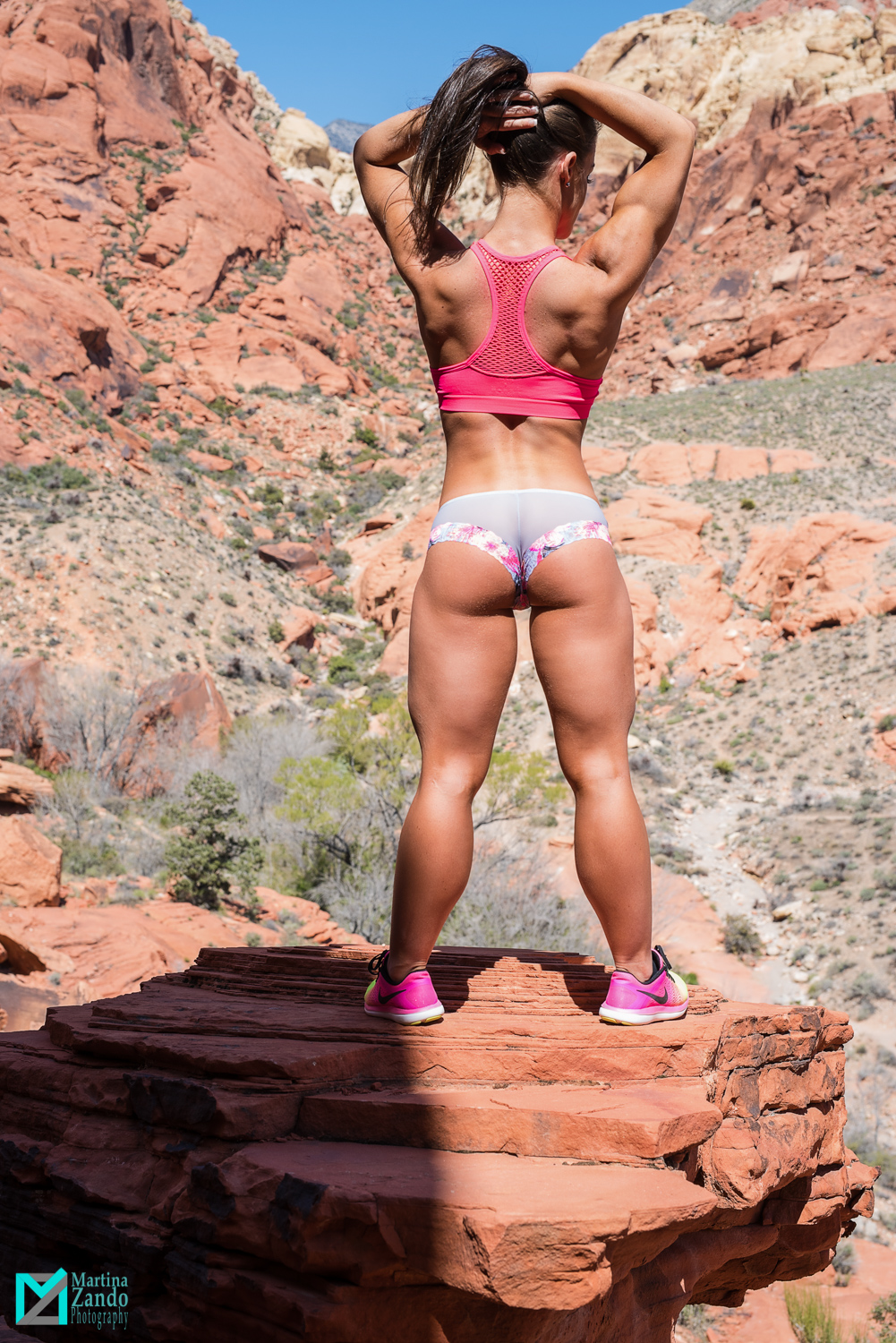 back shot of fitness competitor with desert view