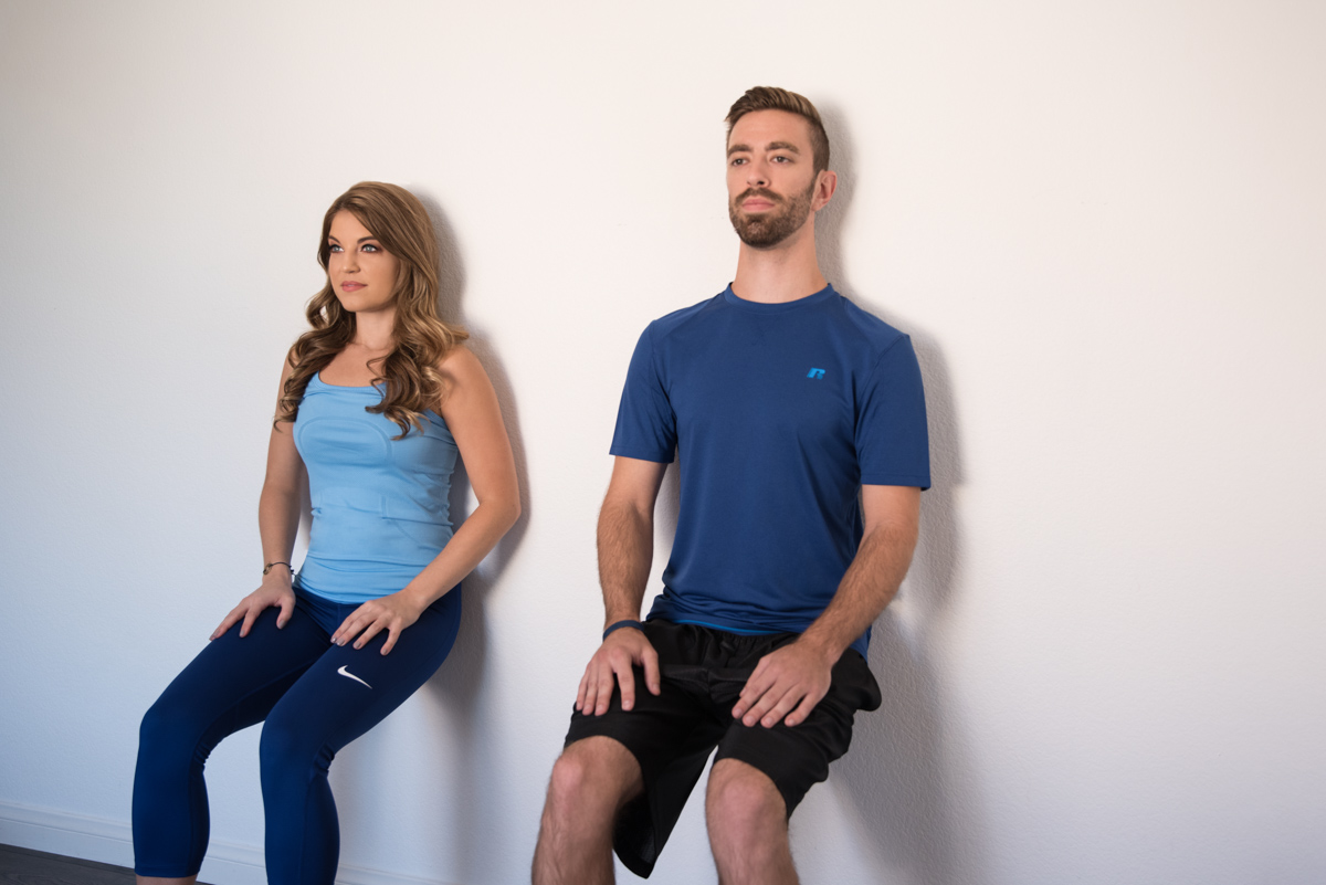 squat on wall two people blue outfits