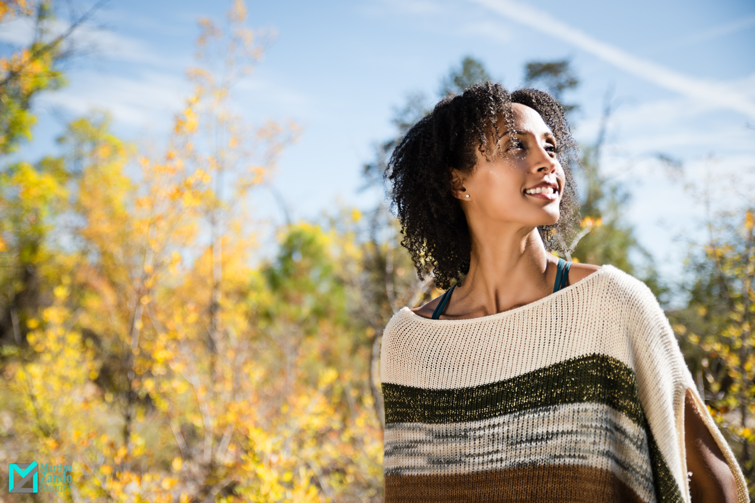 smiling portrait outdoors with white and gold poncho