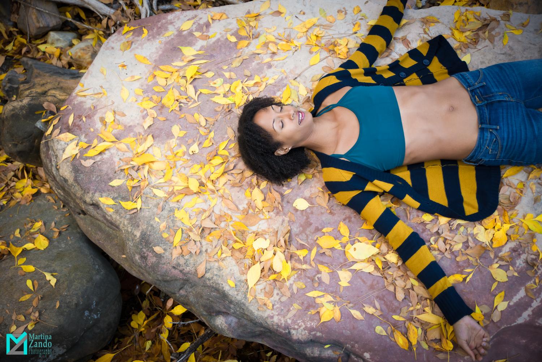 meditation on rock between yellow autumn leaves