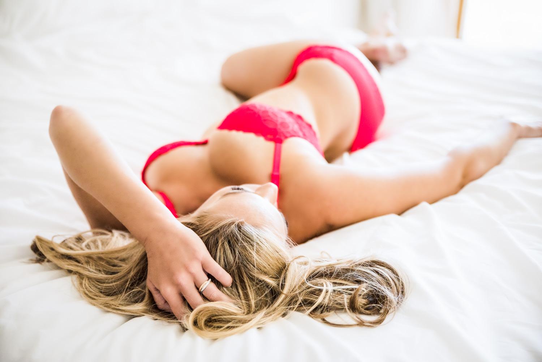 Sensual pose, red lingerie boudoir on white bed