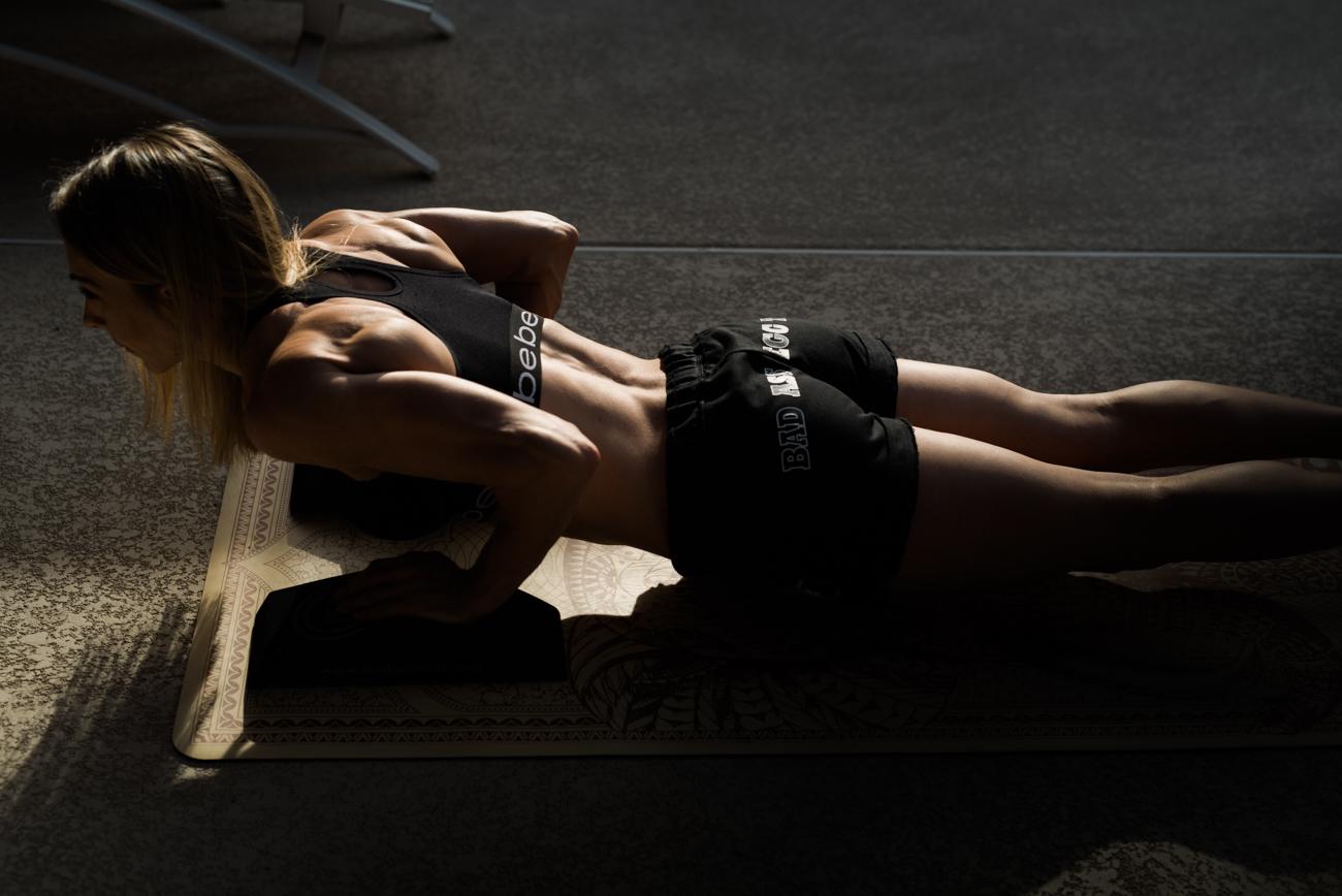 fitness model doing a push up in sunset light