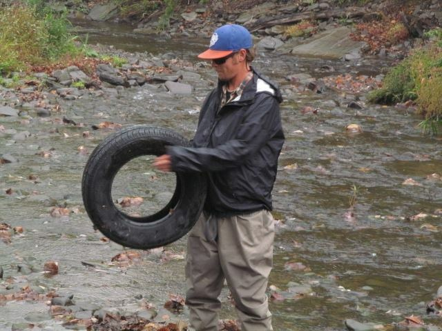 Guide Evan P. removing a tire from Shehawken Creek.