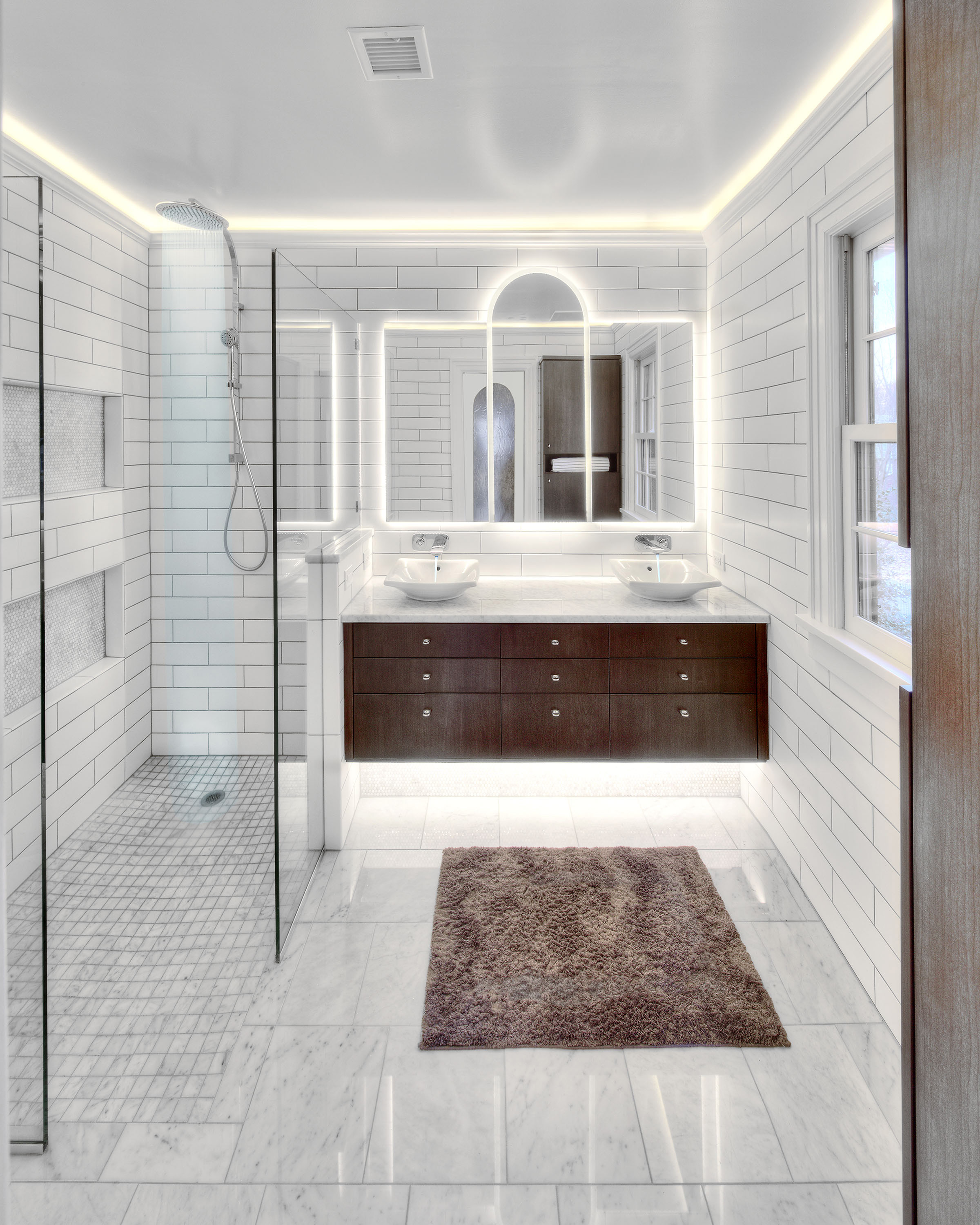 The fixtures have a modern twist and the custom mirror design with integrated lighting is stunning.