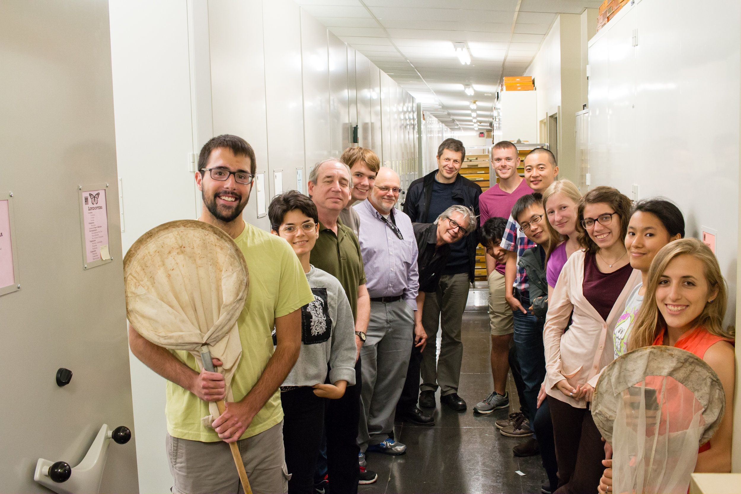 The Academy of Natural Sciences Entomology Community (2017), the group includes a curator, collection manager, curatorial assistants, visiting scholars, visiting PhD students, undergraduate student interns, and volunteers. On either side of the group are cabinets that contain drawers upon drawers of insect research specimens.