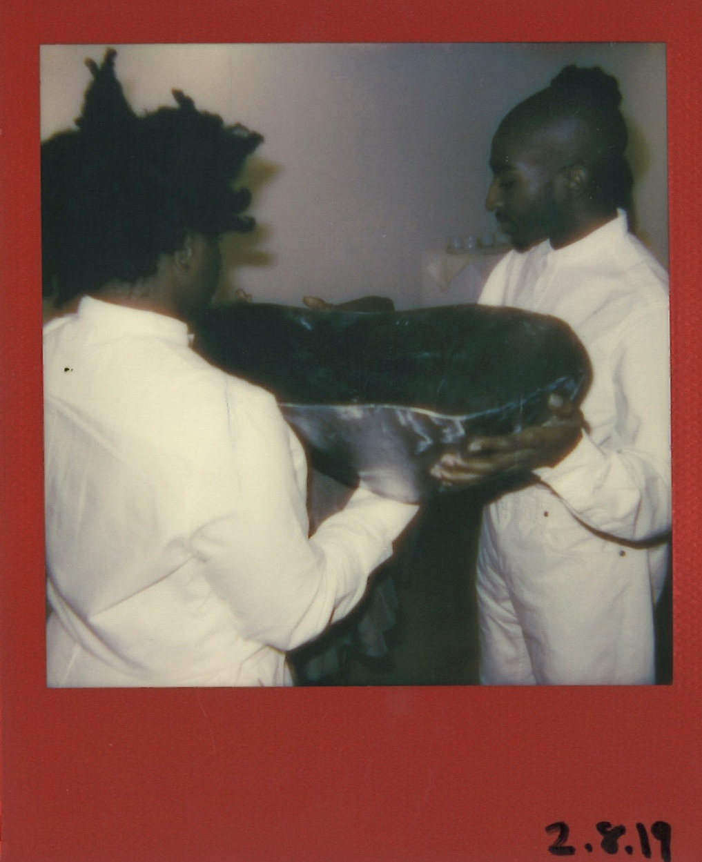 Performance artists Ashley Shey and Maps Glover hold Yacine's Fall's spoon as she unties herself from the 70-pound steel piece. Polaroid for ' FED ' by Maxwell Young