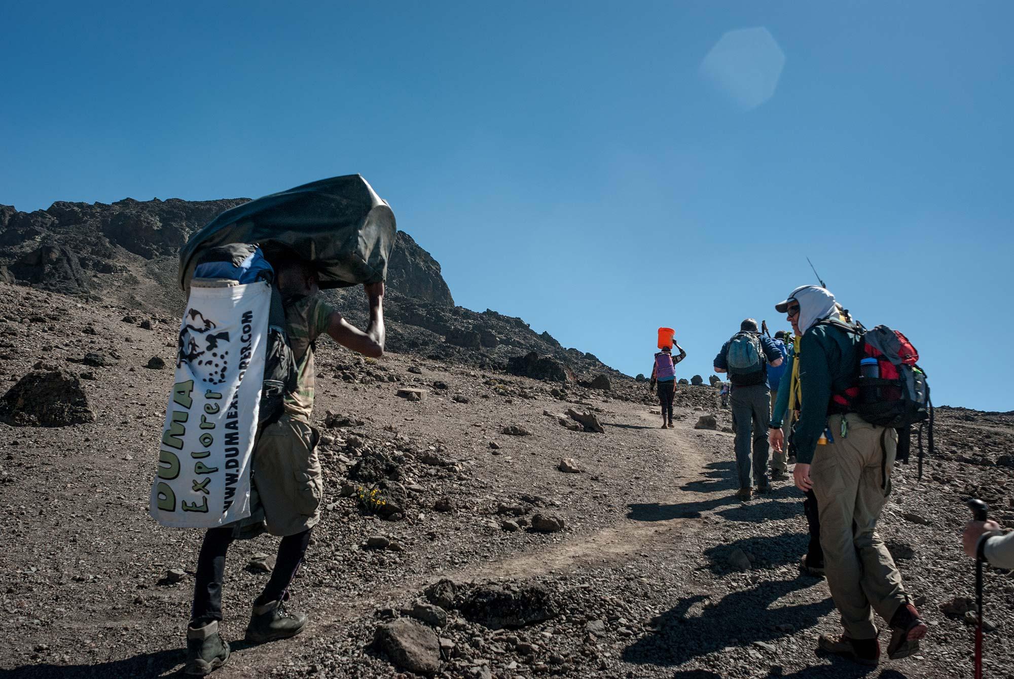 D6-28-dickson-carries-the-team-flag-karanga-to-barufu-camp-kilimanjaro.jpg
