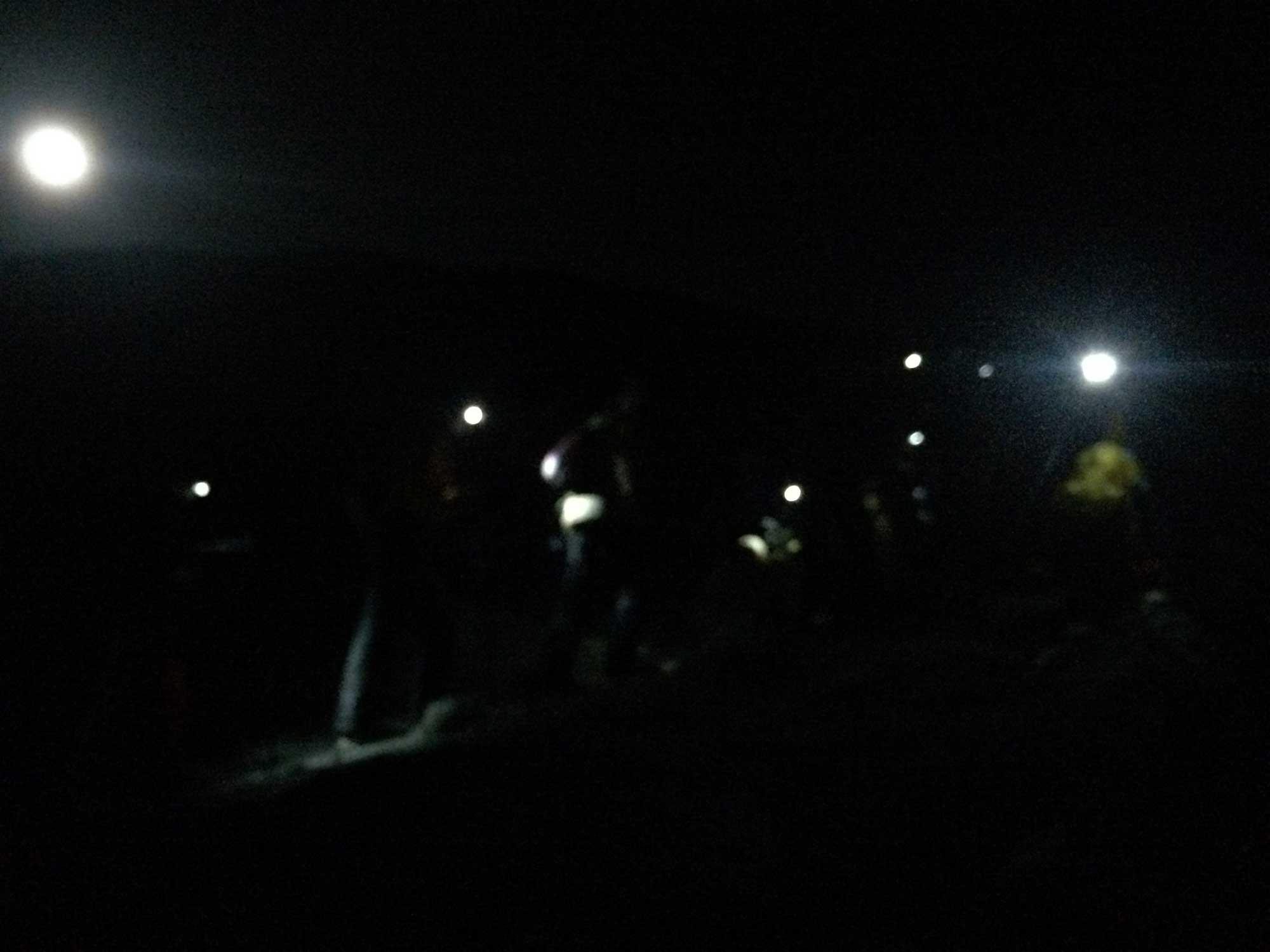 Blur of headlights as Kilimanjaro hikers depart camp for summit.