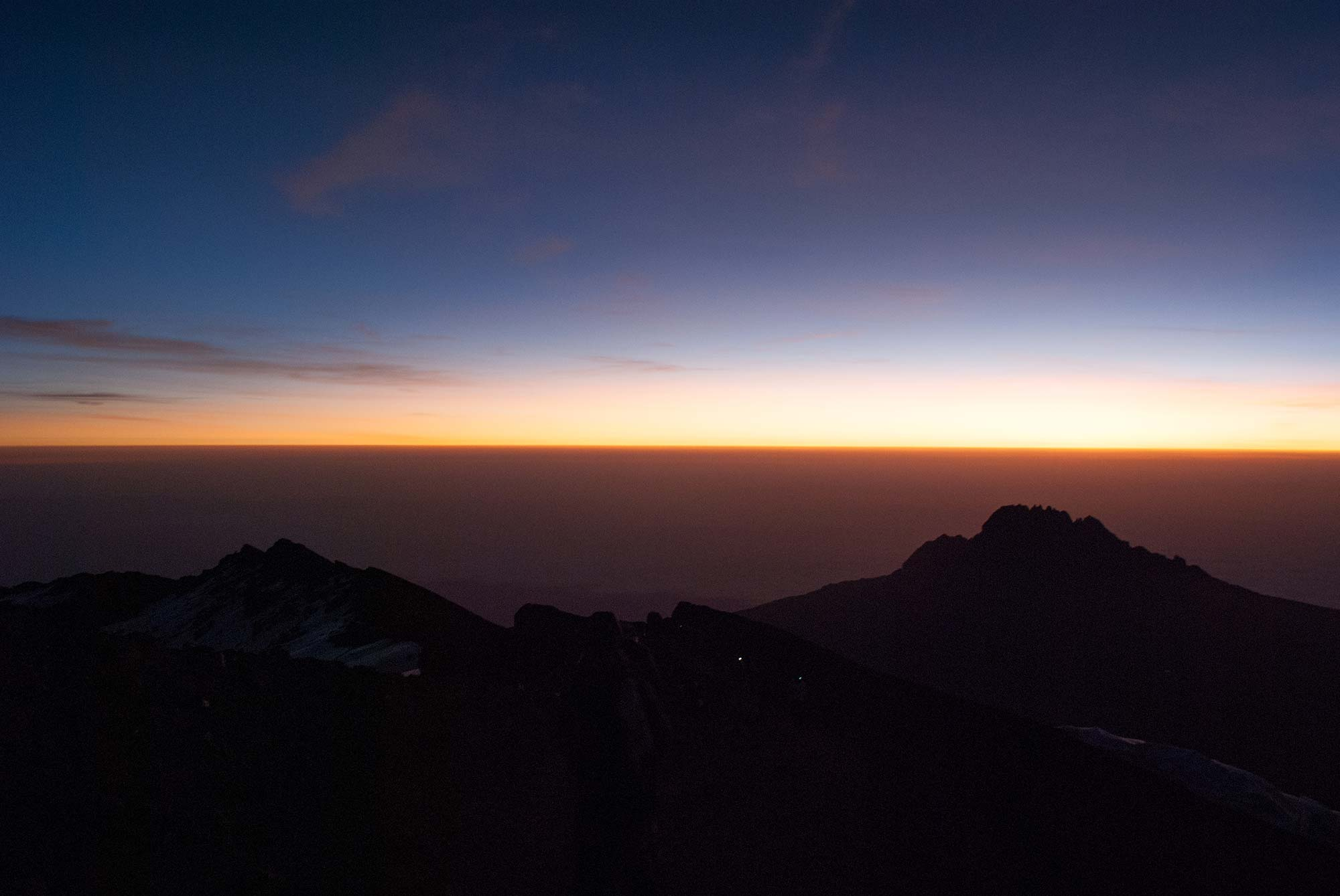 Looking East toward Mawenzi, Kilimanjaro's youngest of its three peaks. The headlamps of two climbers are visible on the mountain.