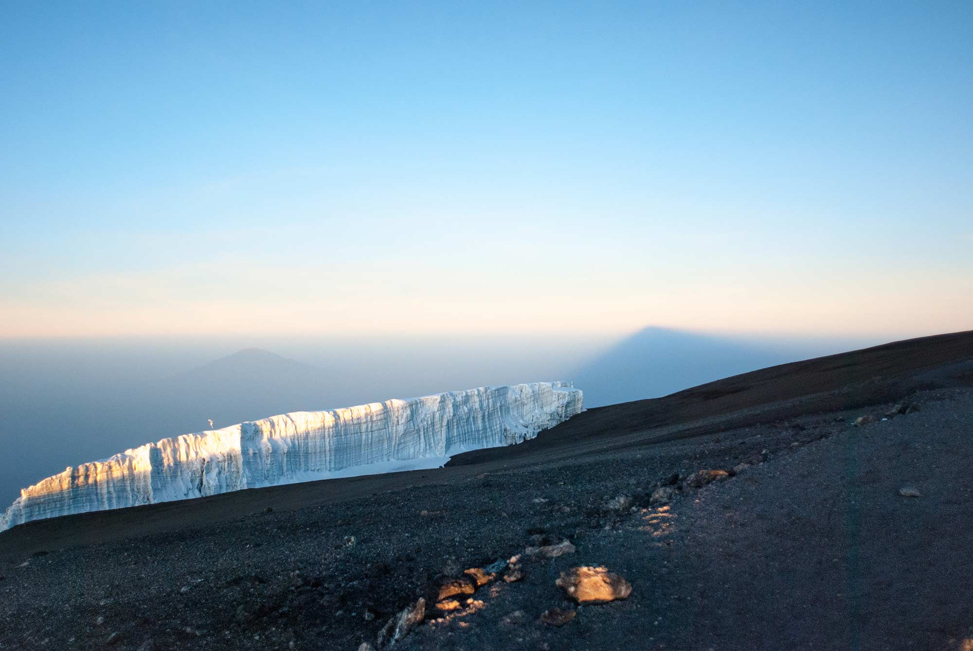 Mount Meru peeks above the glacier. To the right, the shadow of Kibo, Kilimanjaro's tallest peak, stretches to the horizon.