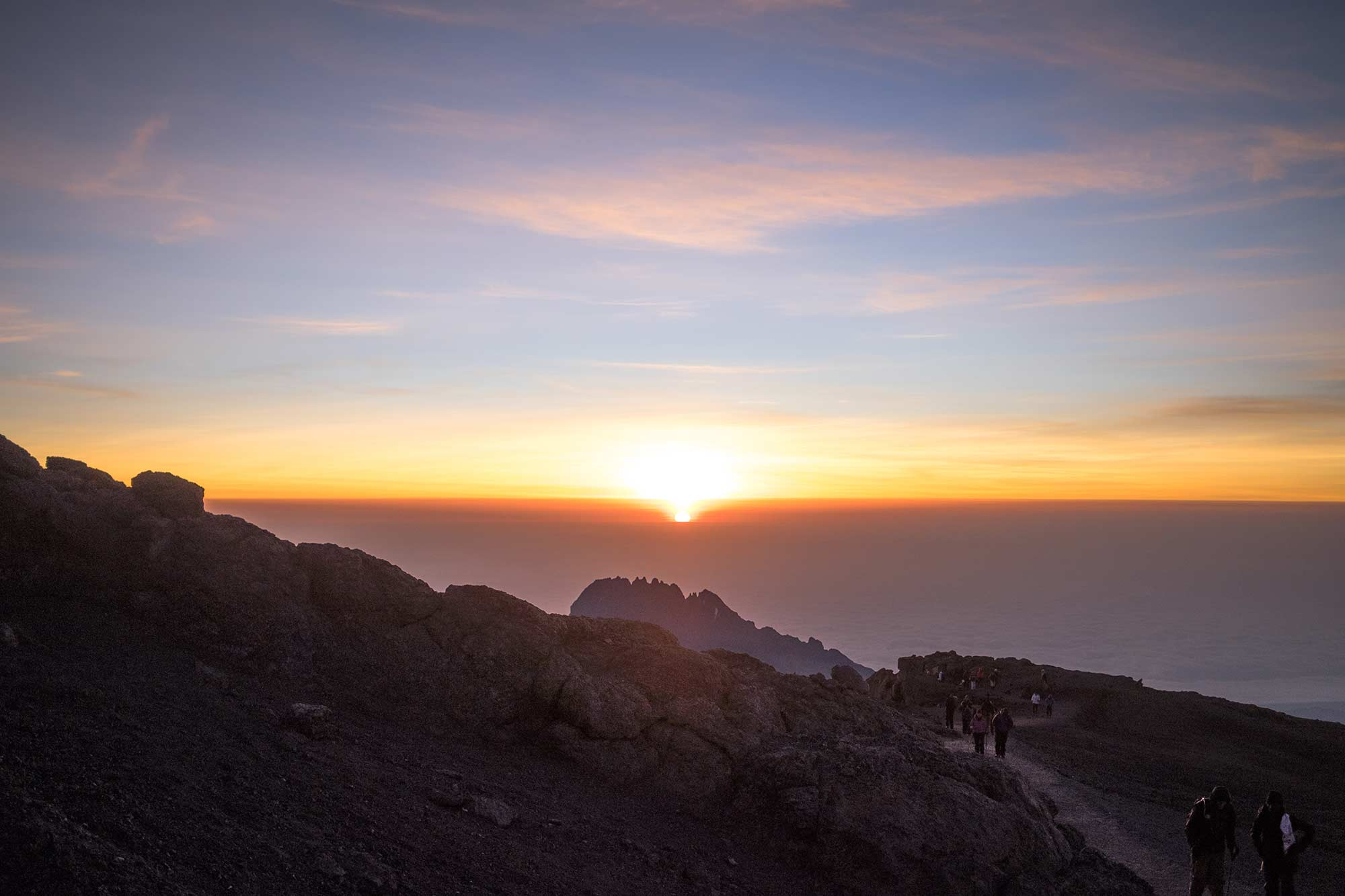 The sun appears on the horizon above Mawenzi, Kilimanjaro's sister peak. Like a great serpent, a line of climbers trudges ever forward.