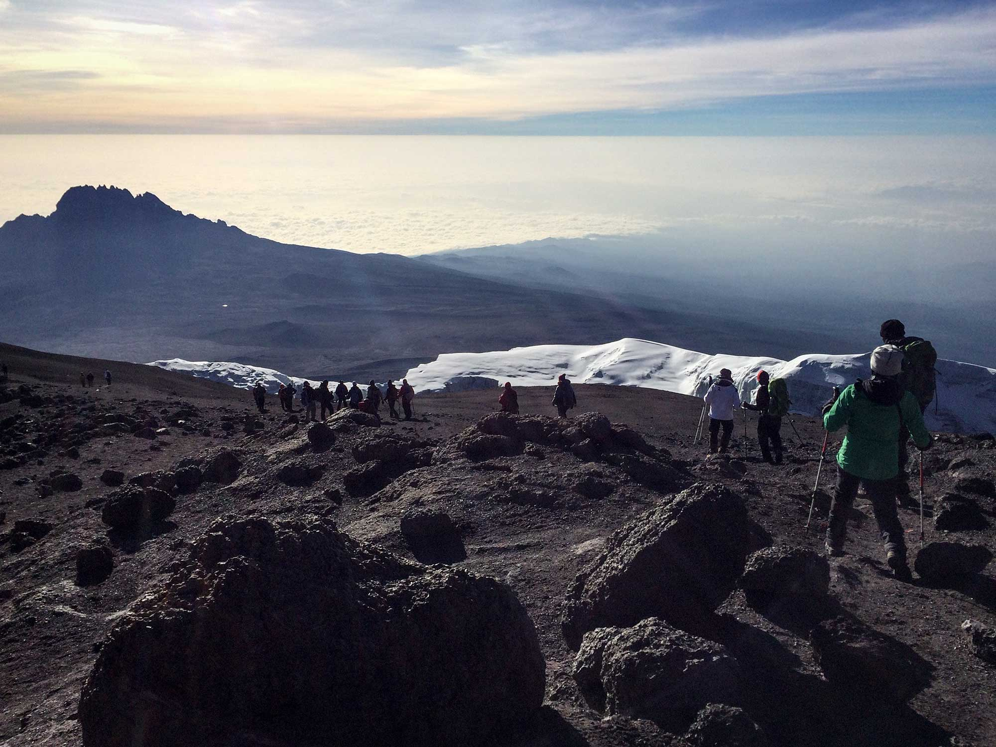 Descending Kilimanjaro to views of glacier, Mawenzi, and clouds as far as the eye can see.