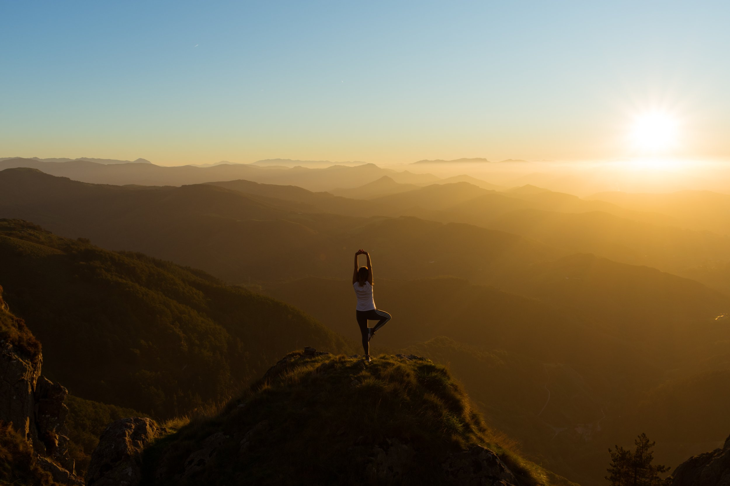 Person doing yoga overlooking mountains