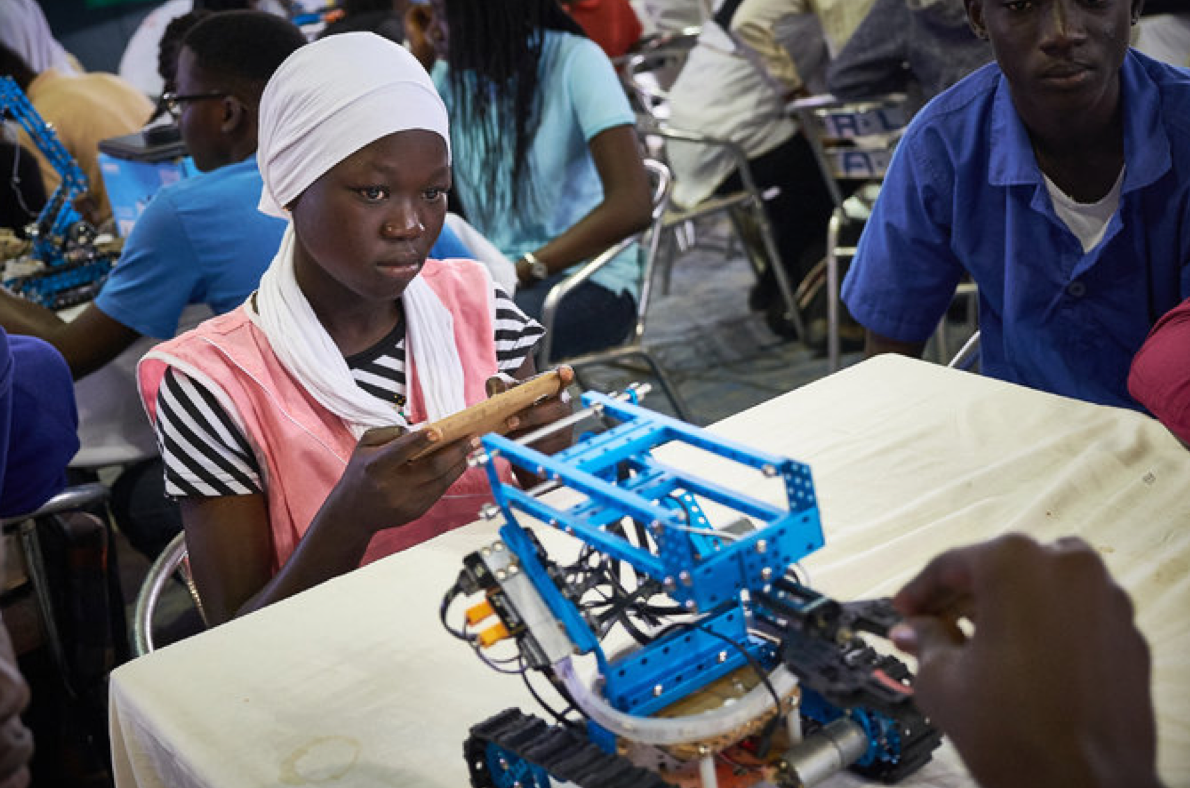 Arame Coumba Dieng testing a robot's mobility with her team from the Lycée de Thiaroye. Credit Sam Phelps for The New York Times