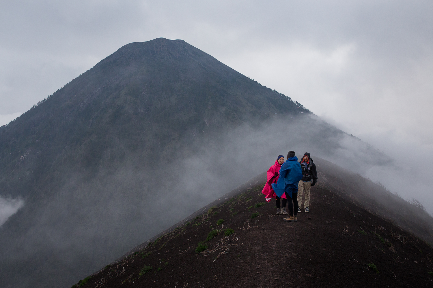 View looking back at Acatenango from the ridge of Fuego. Base camp tarps on Acatenango can be seen above the participants heads.