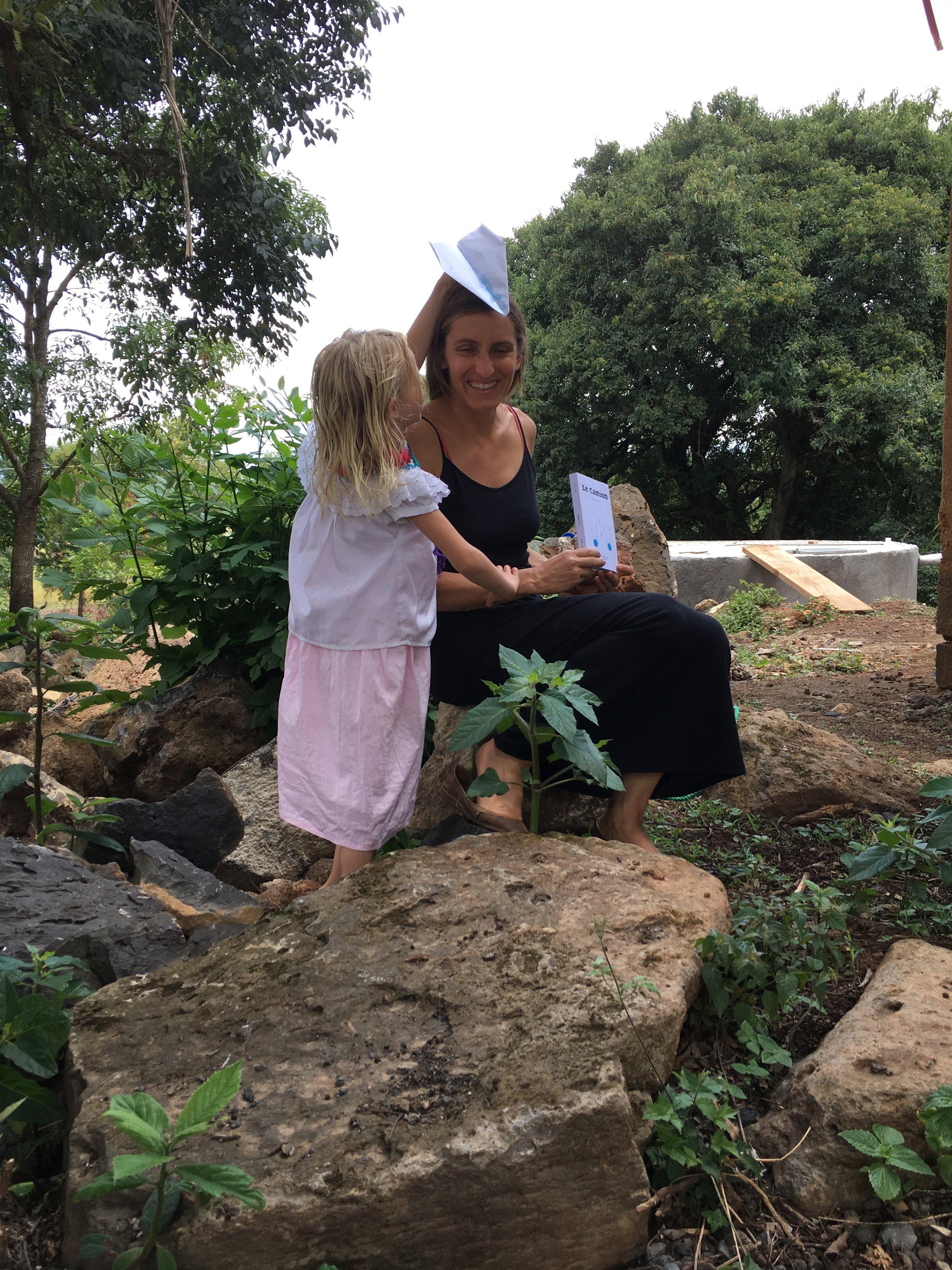 Neige, son livre, sa fille et le petit avion en papier que je lui ai fabriqué, Pátzcuaro, Michoacán, en juin.(Notez le hasard de la chose : nous avons pris cette photo dans le jardin de Neige, dans la langue de la région, le purépecha,Pátzcuaro signifie «lieu des pierres ».)