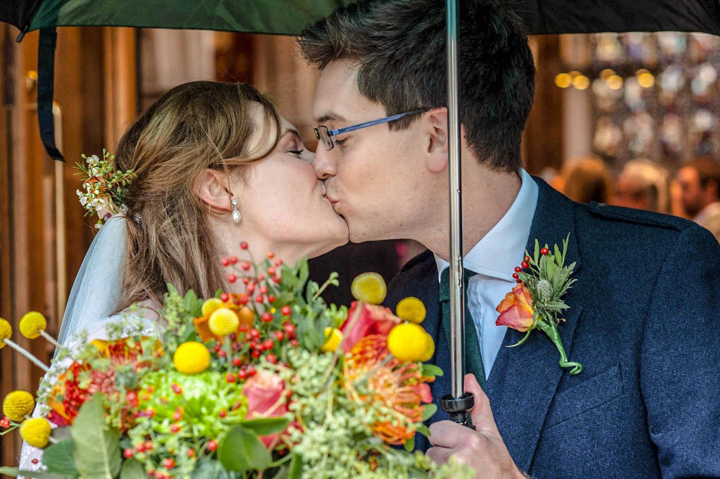 BRIDE-GROOM-KISS-UNDER-BROLLEY.jpg