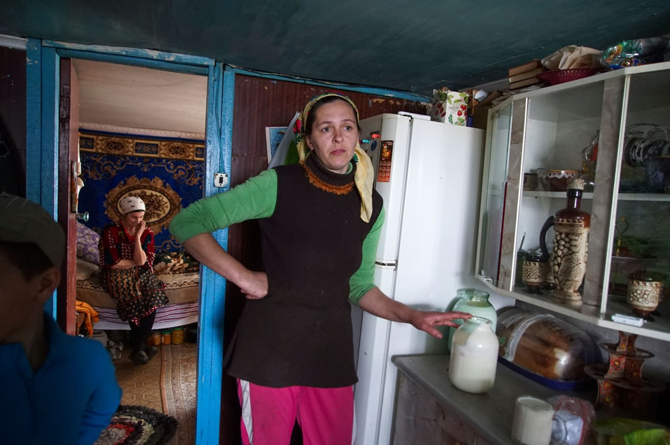 Viktoria Vetrov stands in her kitchen with a jar of fresh cow milk. Photo Credit: Associated Press