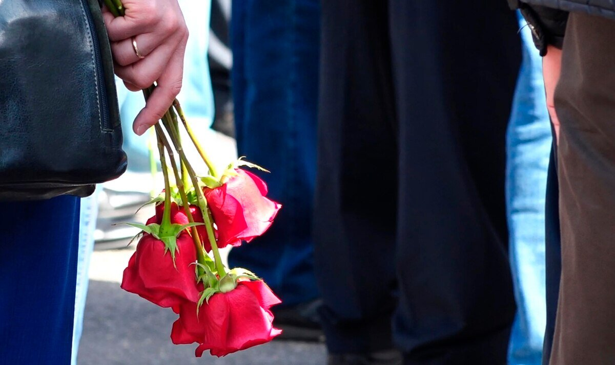 A woman holds roses as she and others gather for the funerals of five Russian nuclear engineers killed by a rocket explosion in Sarov, the closed city which has served as a base for Moscow's nuclear weapons program since the late 1940s. ( Russian State Atomic Energy Corporation ROSATOM via AP )