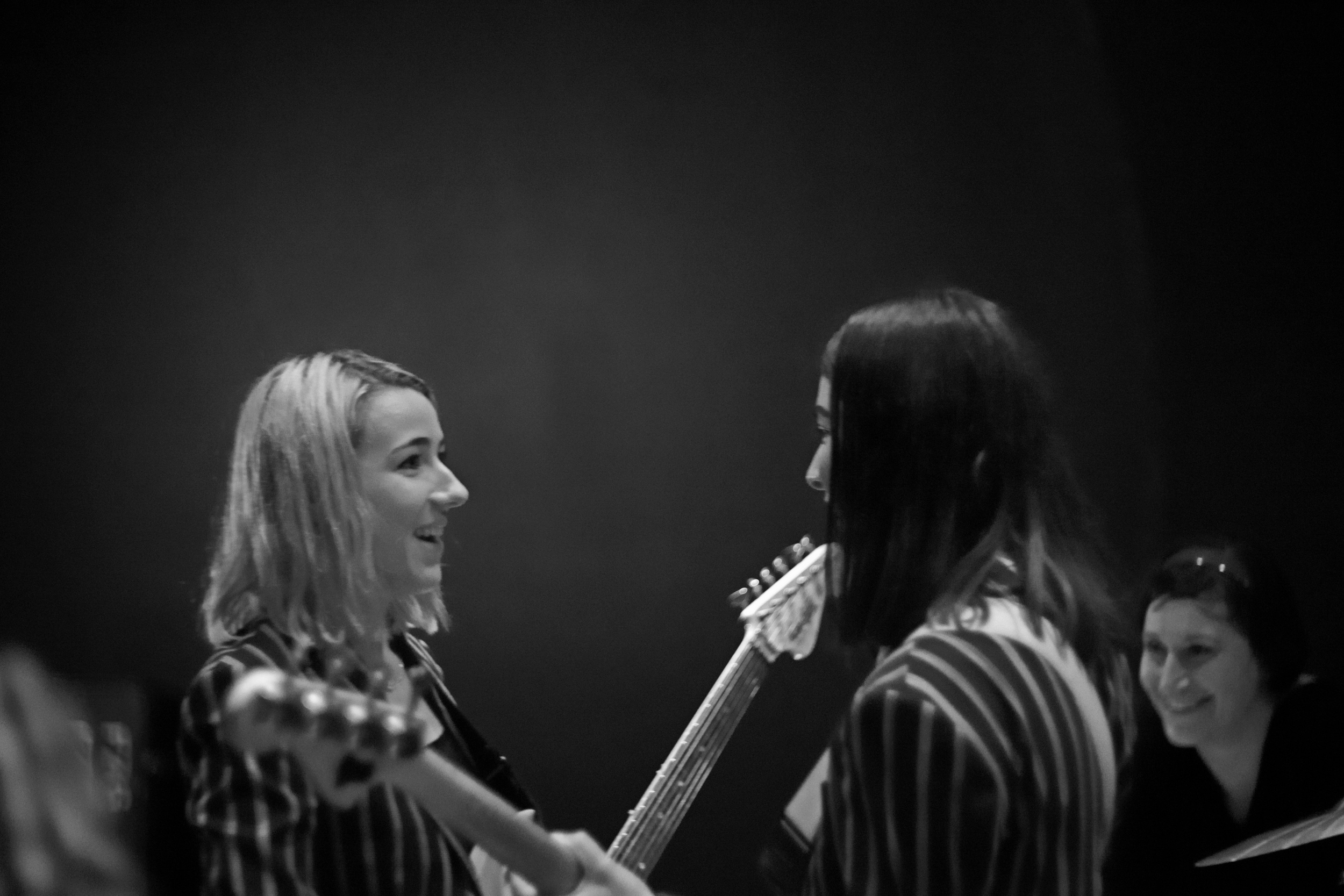 Favorite shot of the night. I like the subtletyof the light coming off the wall behind them. And all three of them look so sincerely happy and unaffected, like they forgot they were onstage in front of an audience. Shutter 1/50, f/1.5, ISO: 1000.