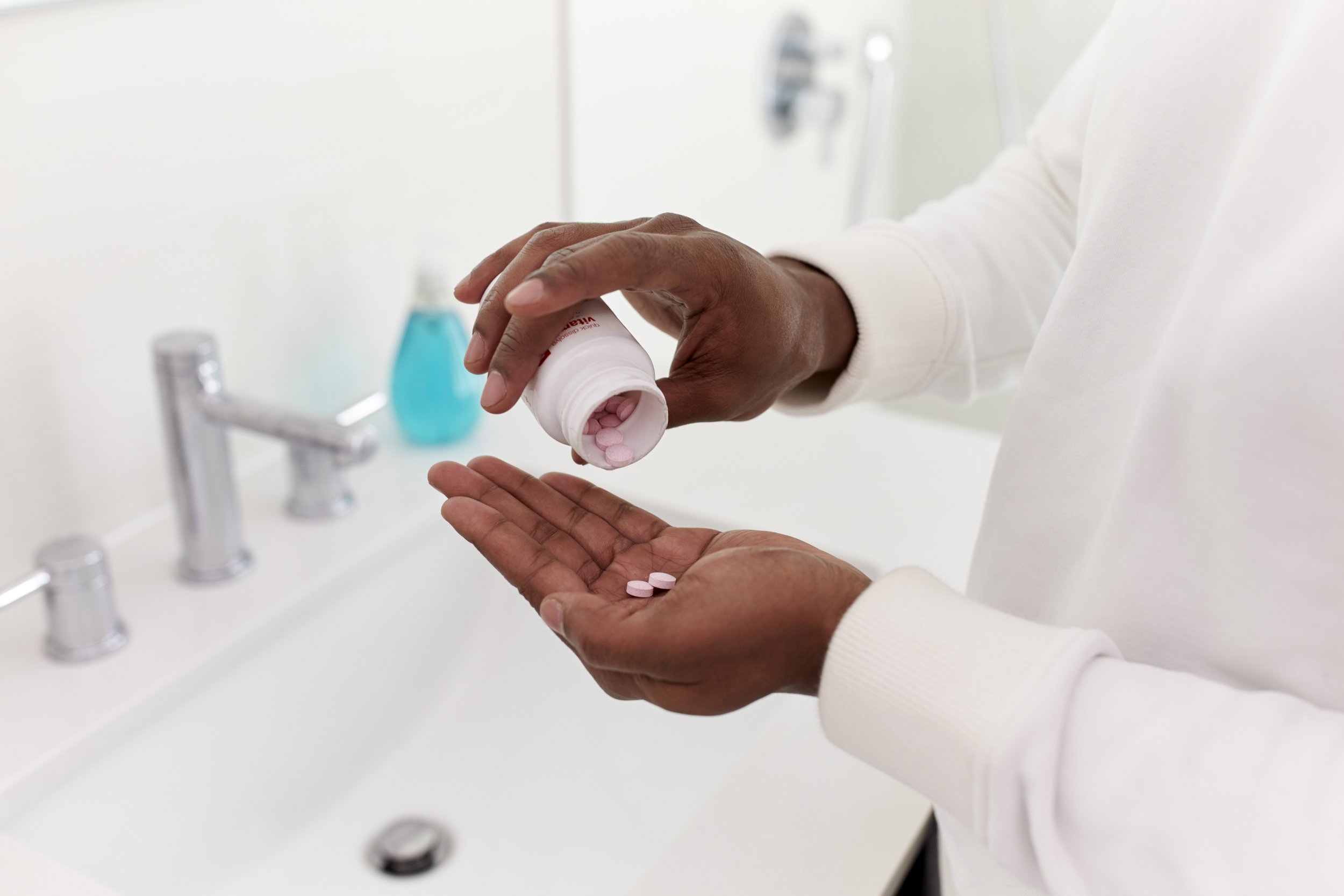 close-up-of-man-in-bathroom-taking-vitamin-56BM7SK.jpg