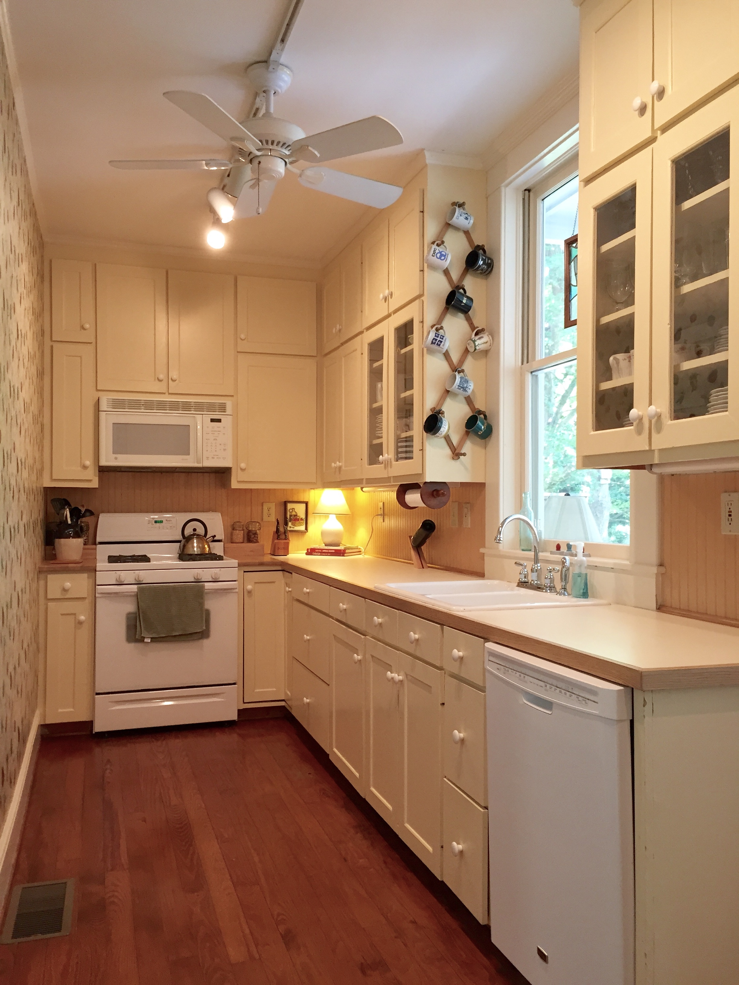 When we started the update, we had simple shaker cabinets with porcelain knobs, laminate countertops, track lighting, a bead board backsplash, and basic white appliances.