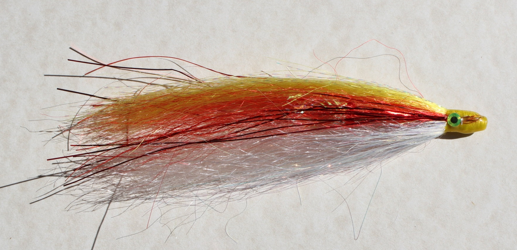 MICKEY FINN, Salmon Series Tube Fly.  Added by requests from Kodiak trollers, this is a gaudy (yellow - red - pearl) pattern that has caught its share of salmon.  These colors contrast well against the blue - gray hues under water.