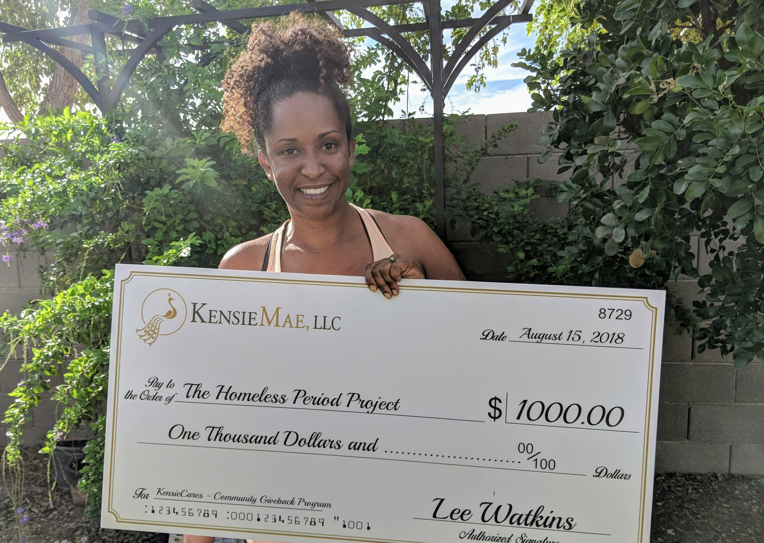 Ona Watkins, HPP - Phoenix Chapter Branch Manager, Holds the donation being Made on behalf of KensieMae employee Lee Watkins for The Homeless Period Project.