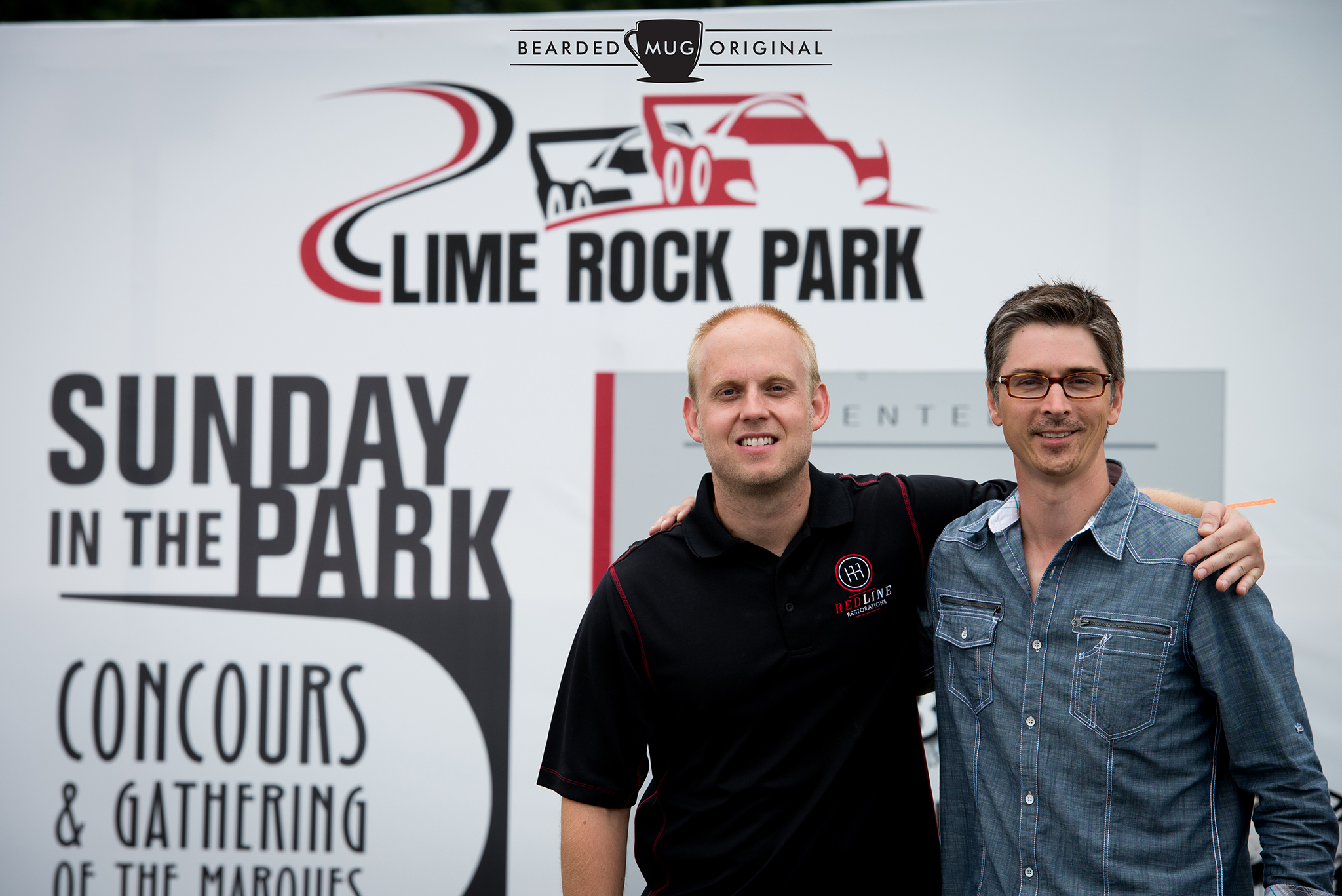 PJ from Redline Restorations and Dwight from The Little Red Racing Car pose in front of the official backdrop.