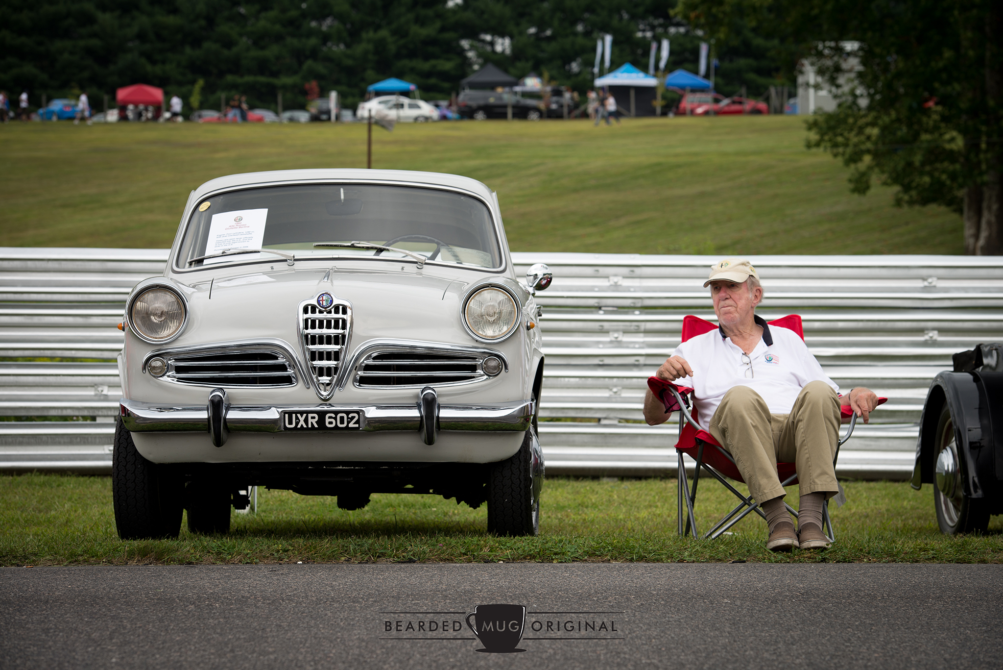 The presumed owner of this 1960 Alfa Romeo Giulietta Berlina enjoys a relaxing bit of time next a all-original Italian classic.