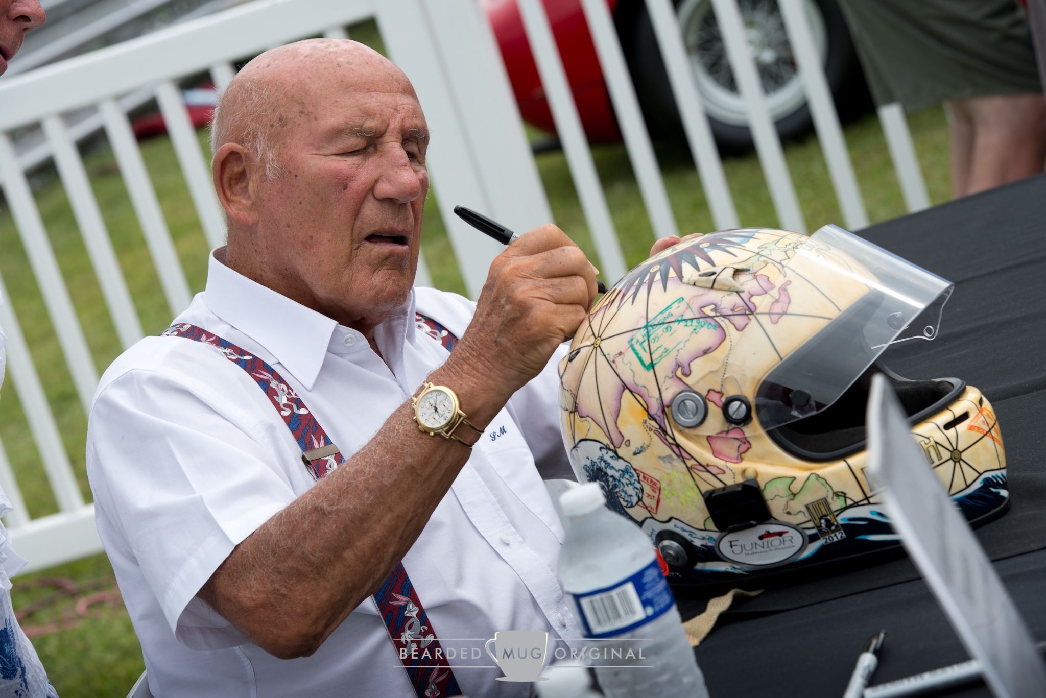 Sir Stirling Moss, the Honored Guest, was presented with a variety of memorabilia for him to apply his signature to.
