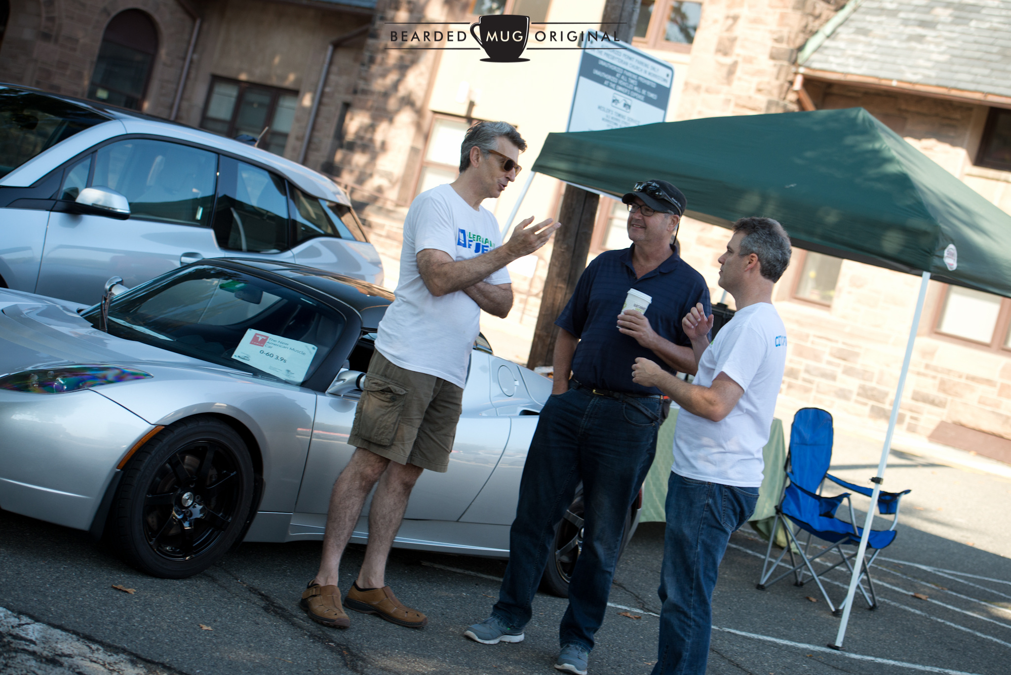 Main organizer Chris Neff (l.) and Paul Miller, president of Sustainable Morristown (r.) discuss the installation of public chargers in town with Morristown's Mayor Tim Dougherty (c.)in front of a Tesla Roadster, the first car offered by the trailblazing marque.