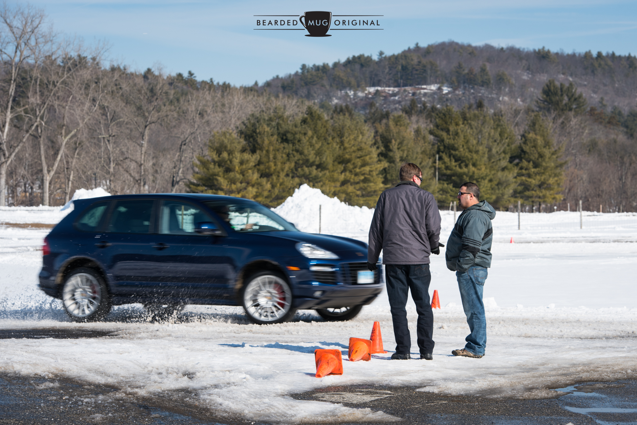 Travis and another gent stand calmly at the track access while a rip-roaring Cayenne slides past.