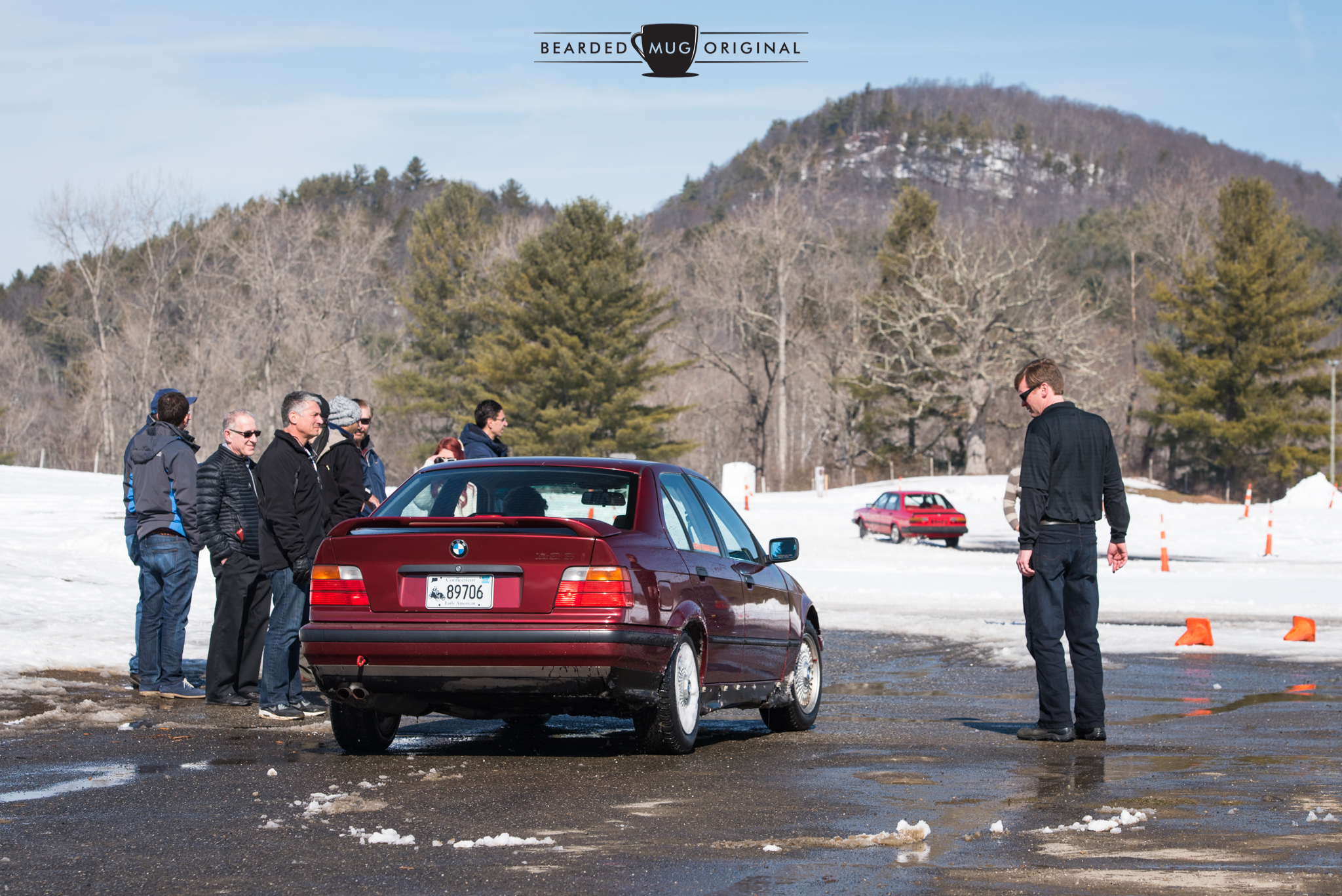Eager drivers huddle for warmth as they await their turn behind the wheel of the red E36.