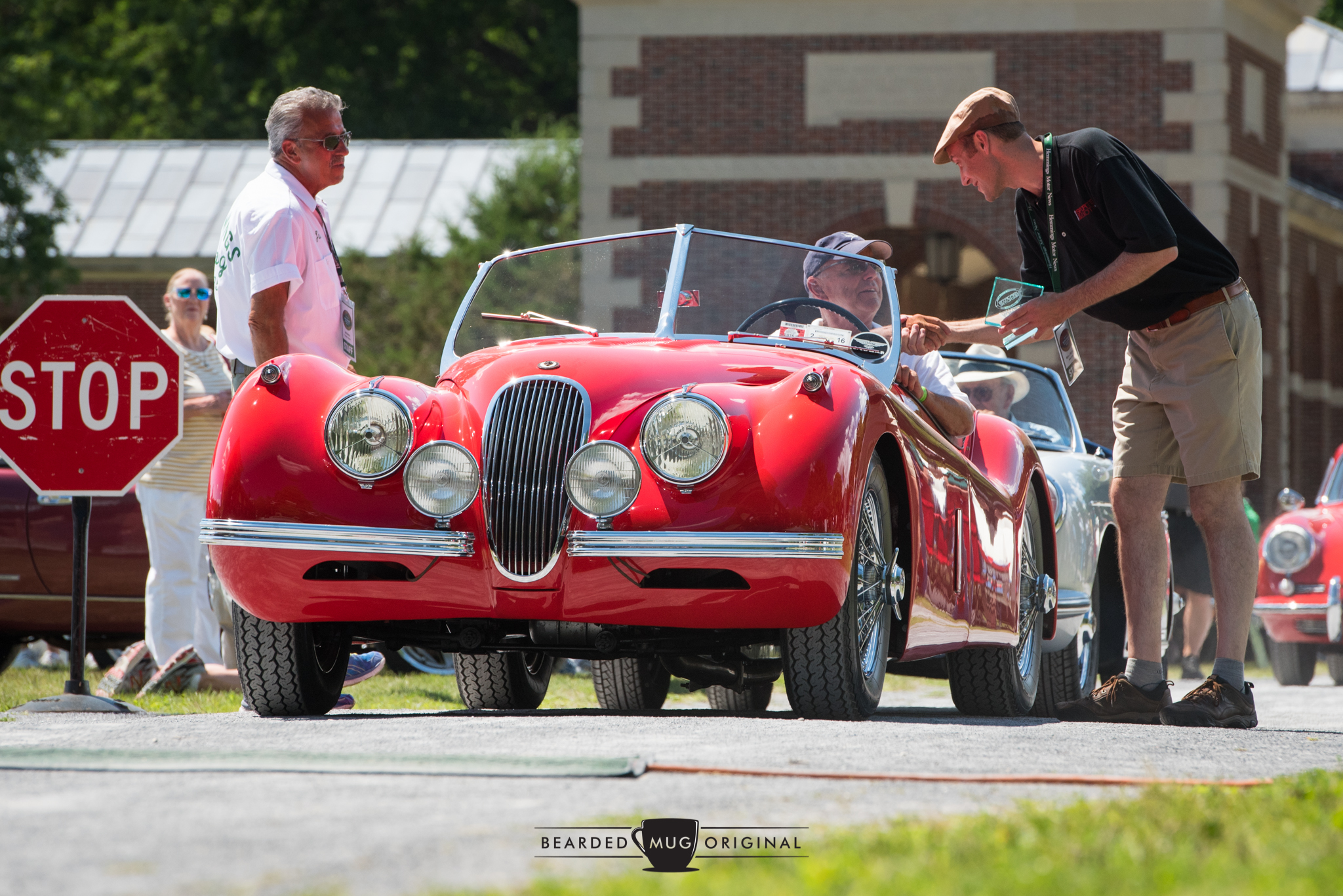 Publisher Jim Menneto (l.) and Mark J. McCourt (r.) present this beautiful Jaguar XK120 with a well-deserved award at the 2016 Sports & Exotic Show.