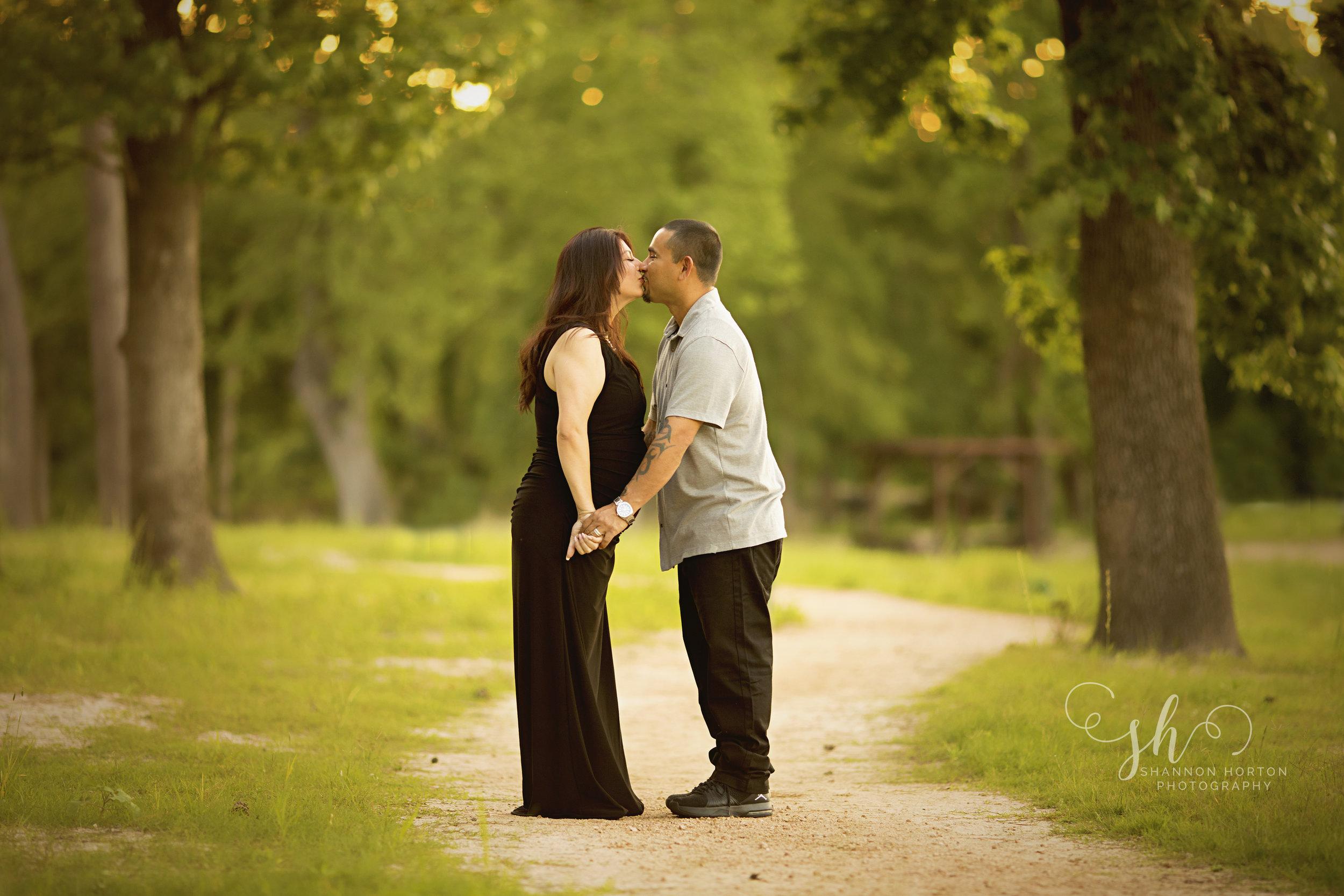 pregnant-couple-kisses-along-gravel-walkway