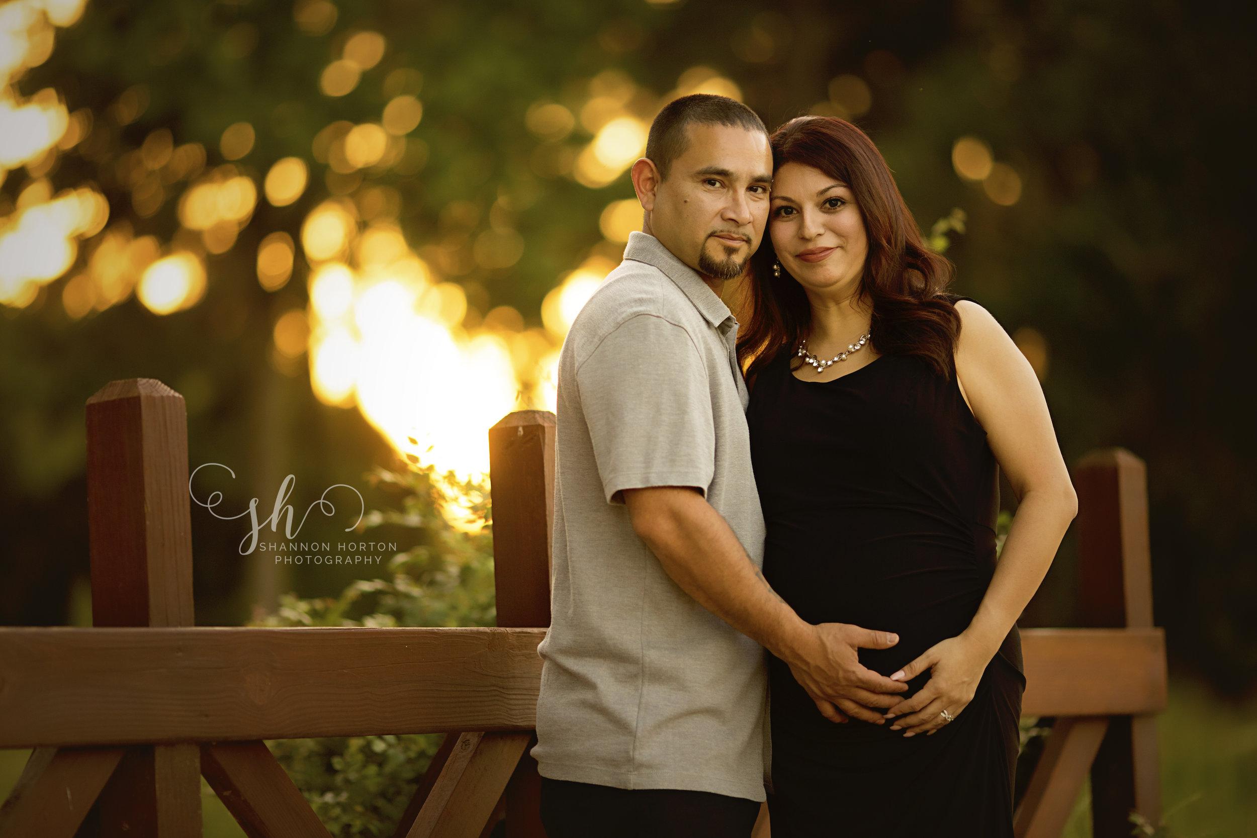 pregnant-couple-standing-on-bridge