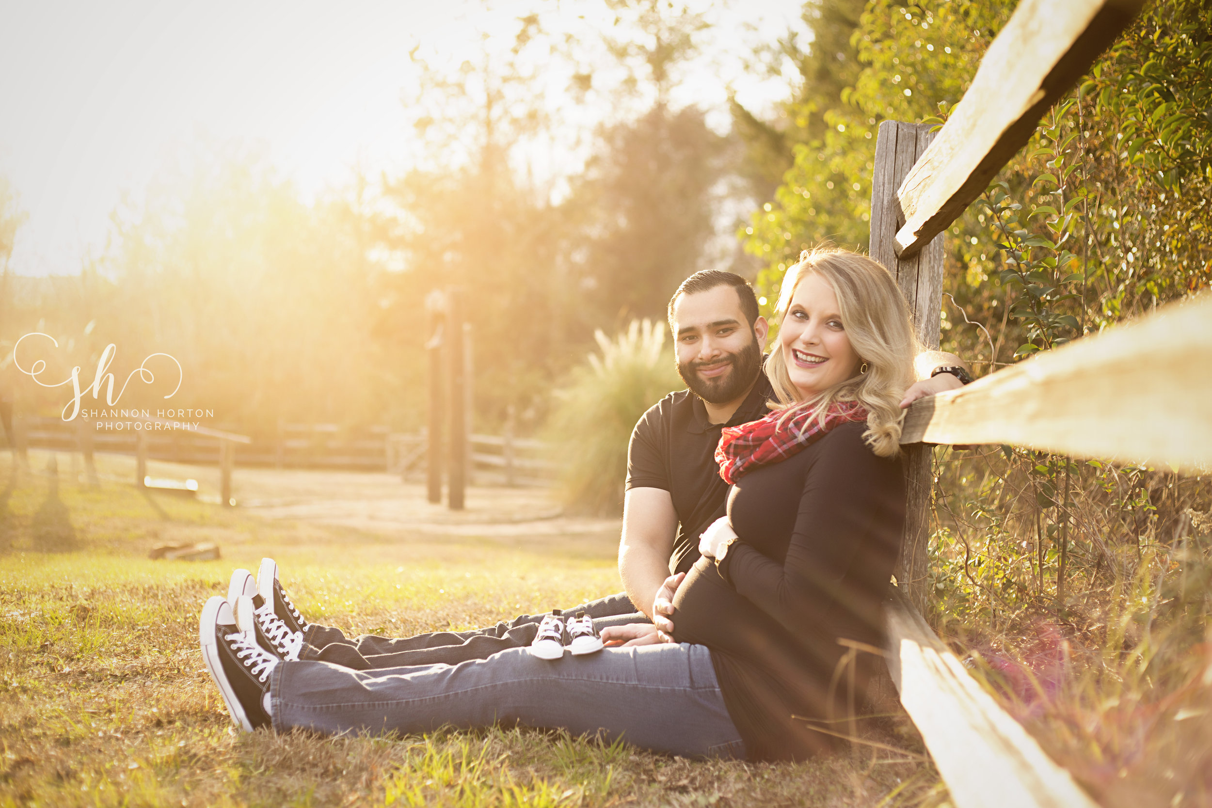 expecting-couple-sit-along-wooden-fence