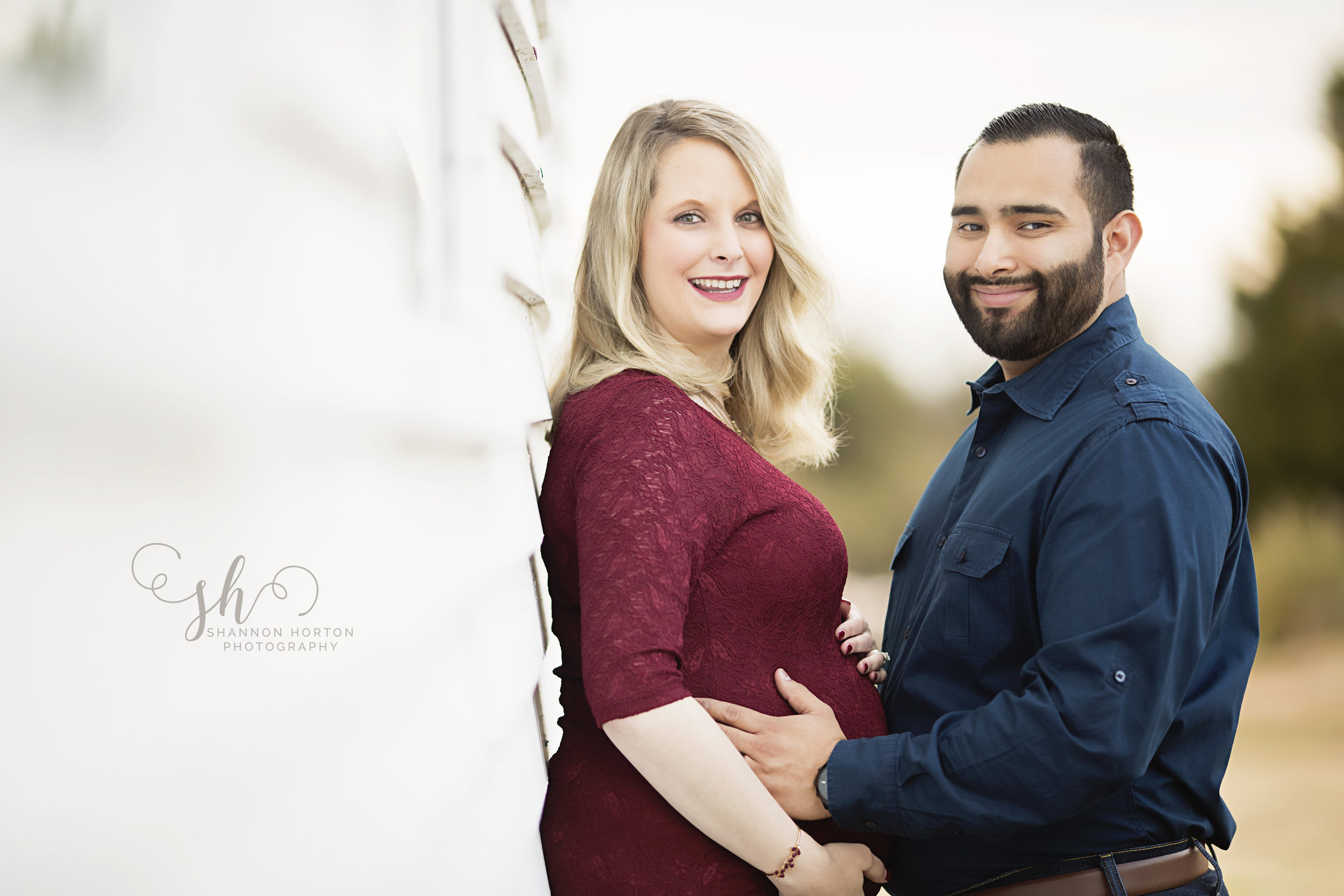 pregnant-couple-standing-against-white-building