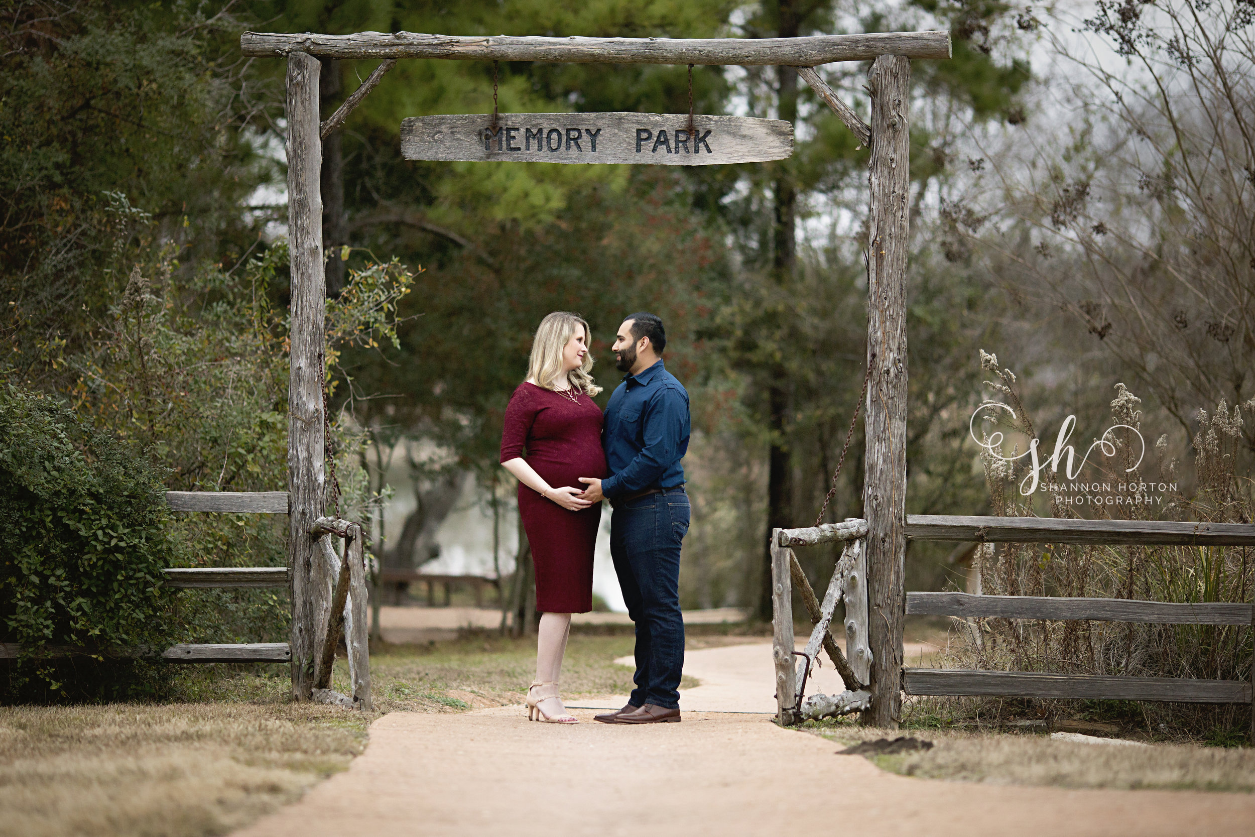 pregnant-couple-standing-under-memories-sign
