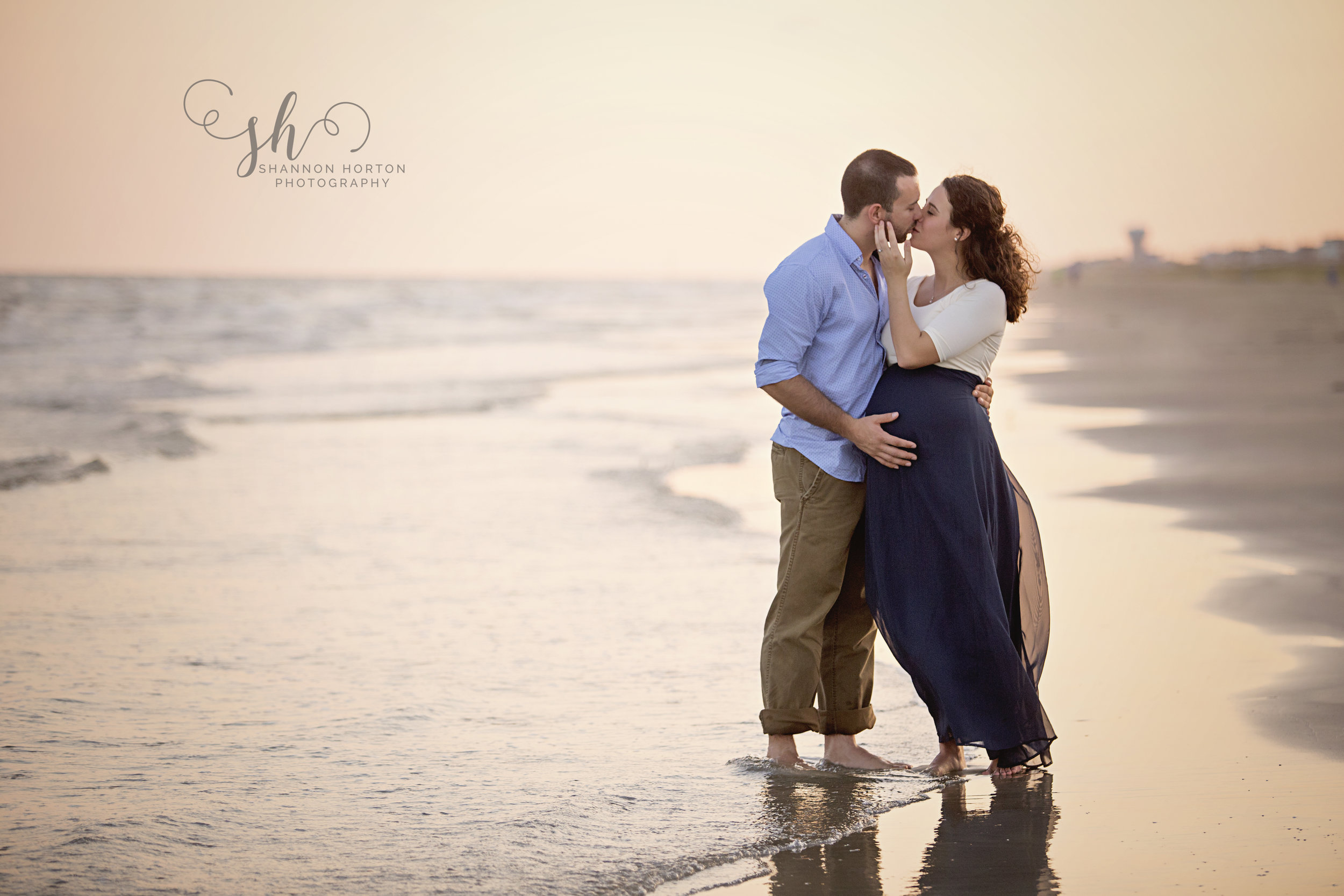 pregnant-mother-kissing-husband-on-beach