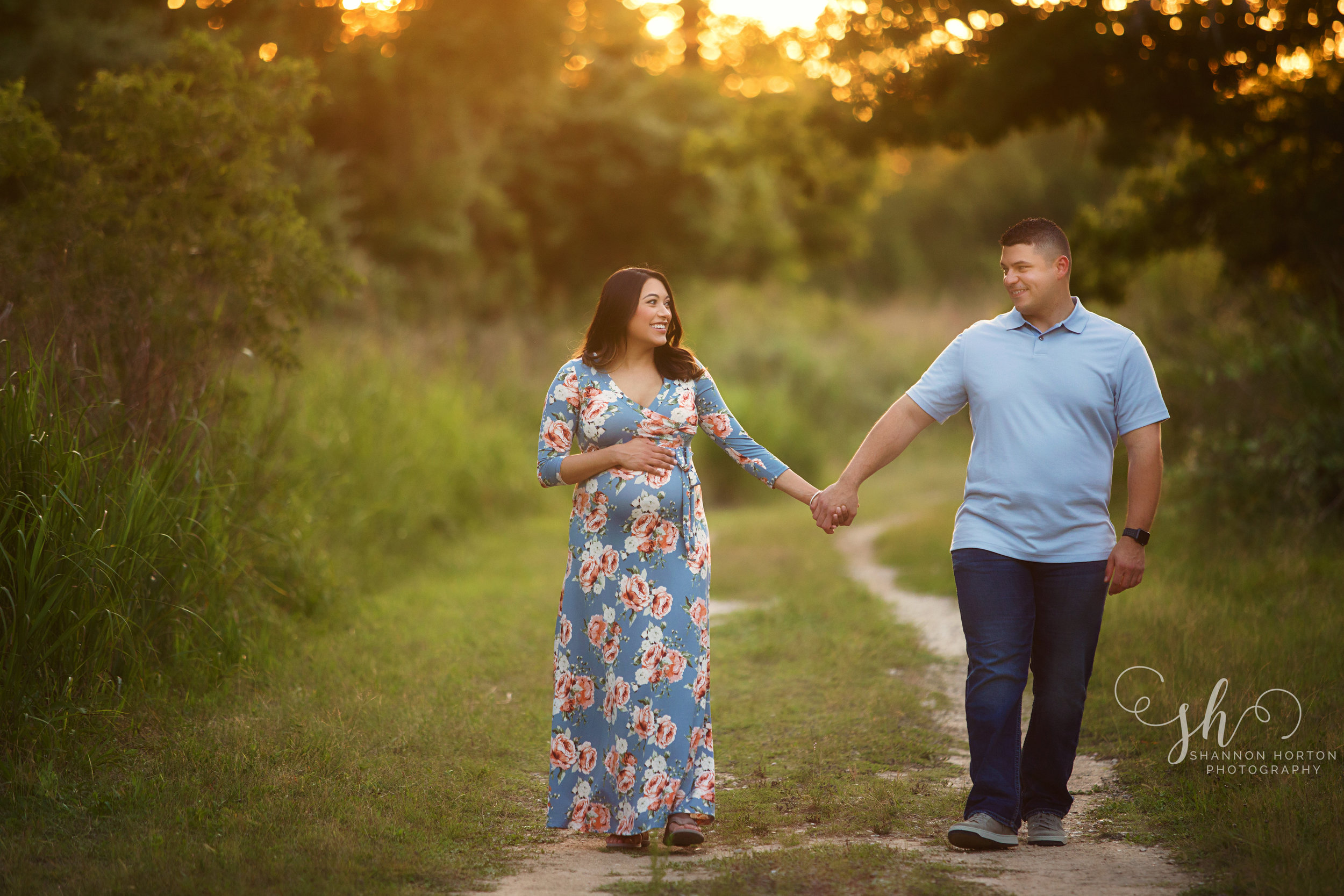 expecting-couple-walking-along-grassy-path