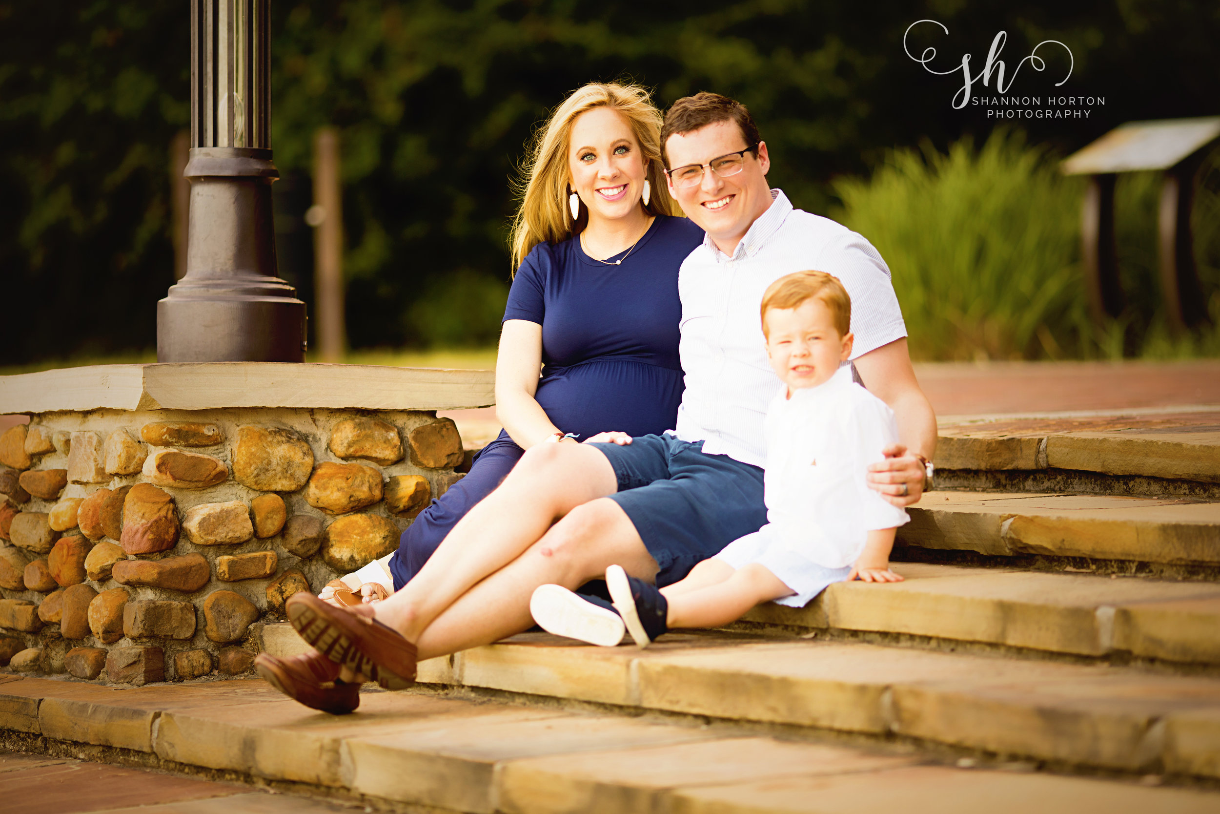 expectant-couple-sitting-on-rock-stairs-with-toddler