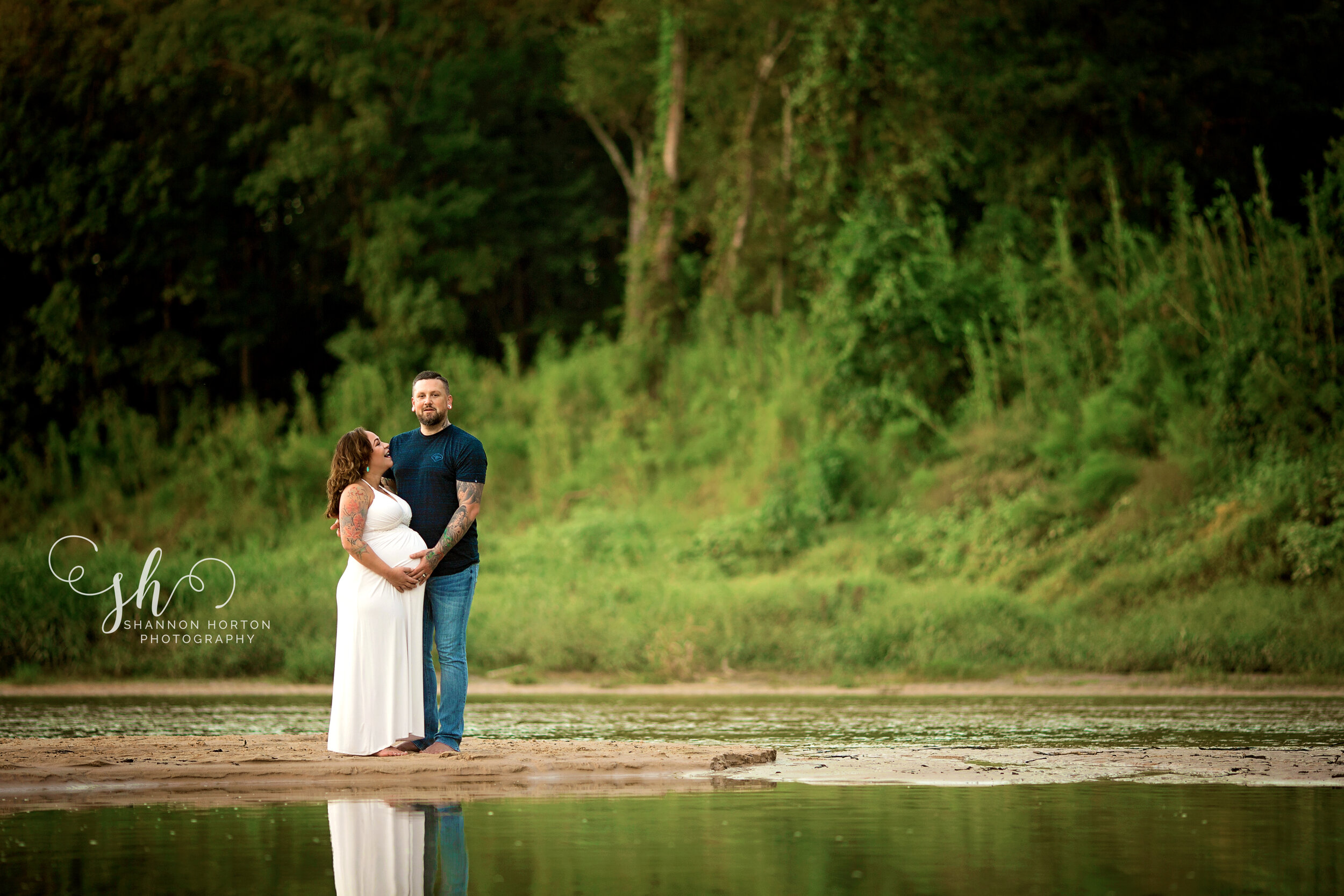pregnant-couple-standing-at-edge-of-creek