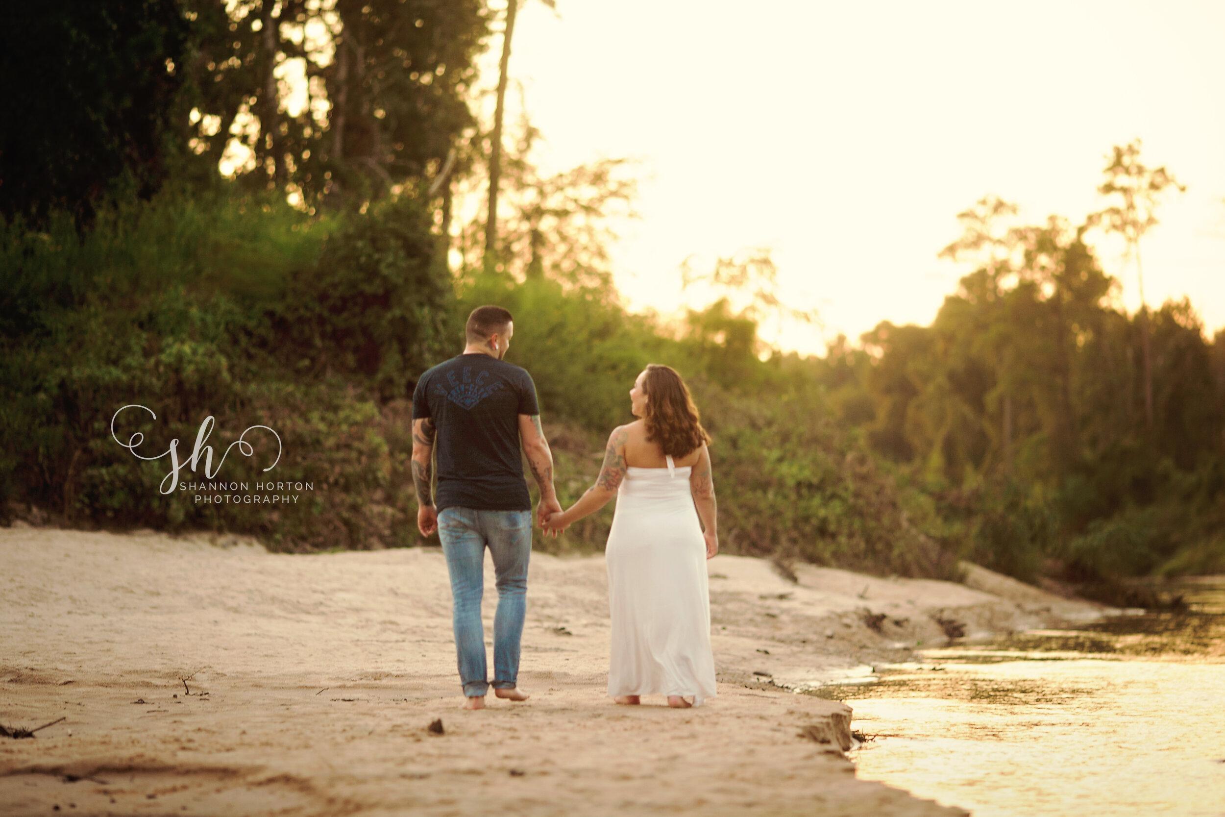 husband-and-wife-walking-along-creek-bank