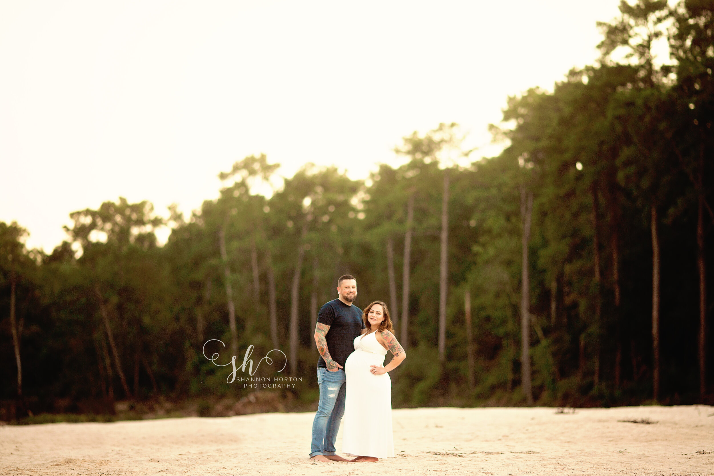husband-and-pregnant-wife-posed-in-sand
