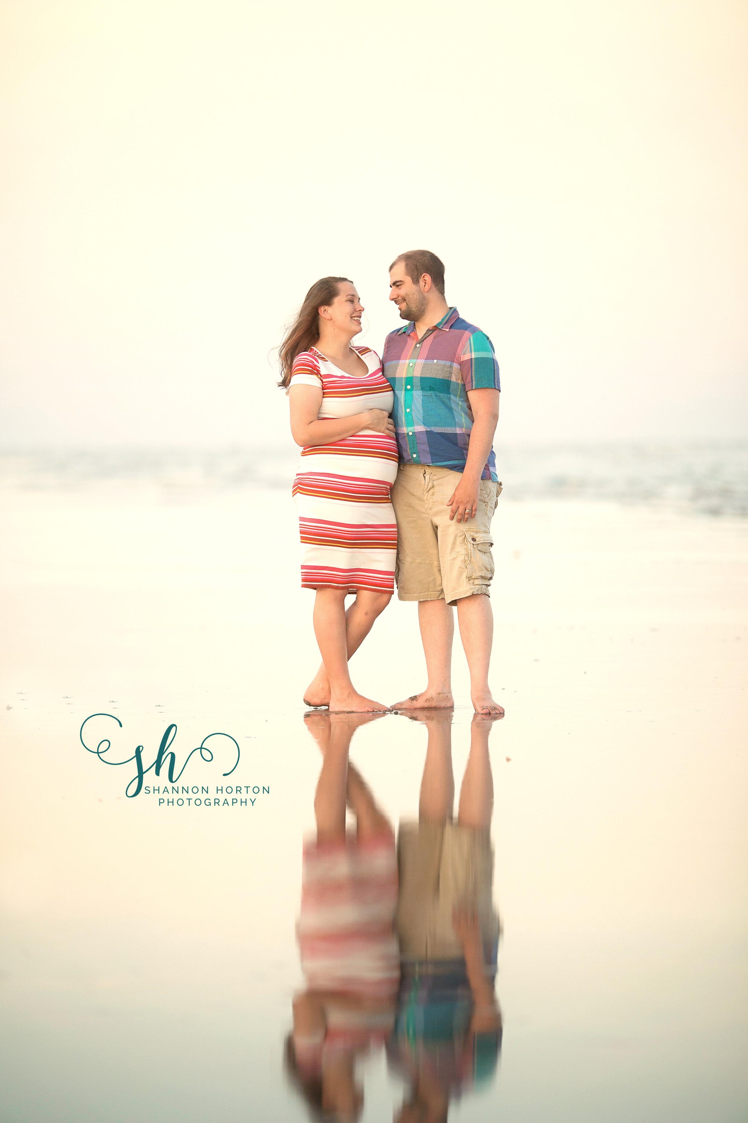 expectant-couple-face-each-other-on-beach