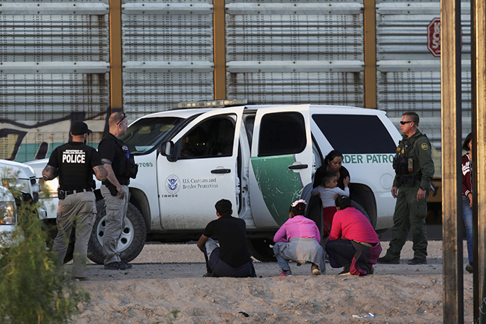 An immigrant family is detained by the US Customs and Border Protection officials after crossing into the United States and turning themselves in to request asylum in El Paso, Texas, as seen from Ciudad Juarez in Mexico on Tuesday 9 July. [Photo: Daniel Becerril/Reuters]