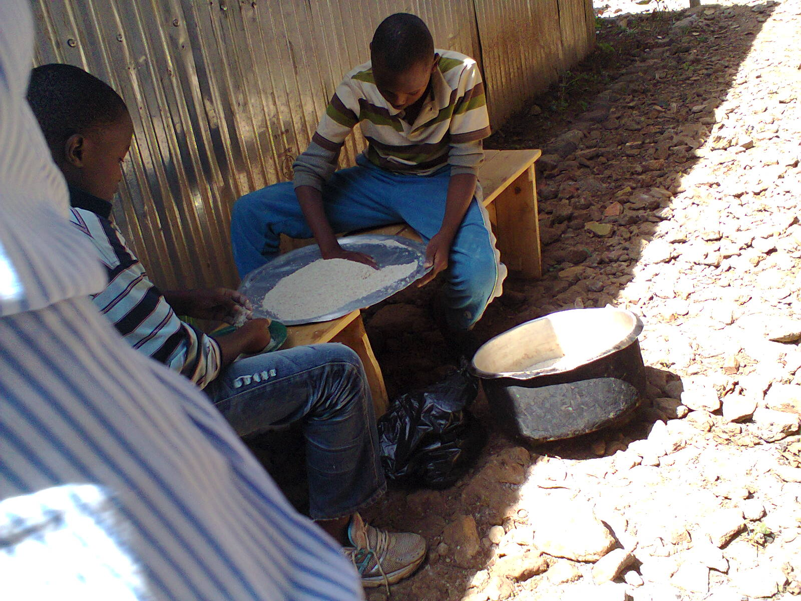 Alex & Kamaru preapring rice for cooking for the boys.jpg